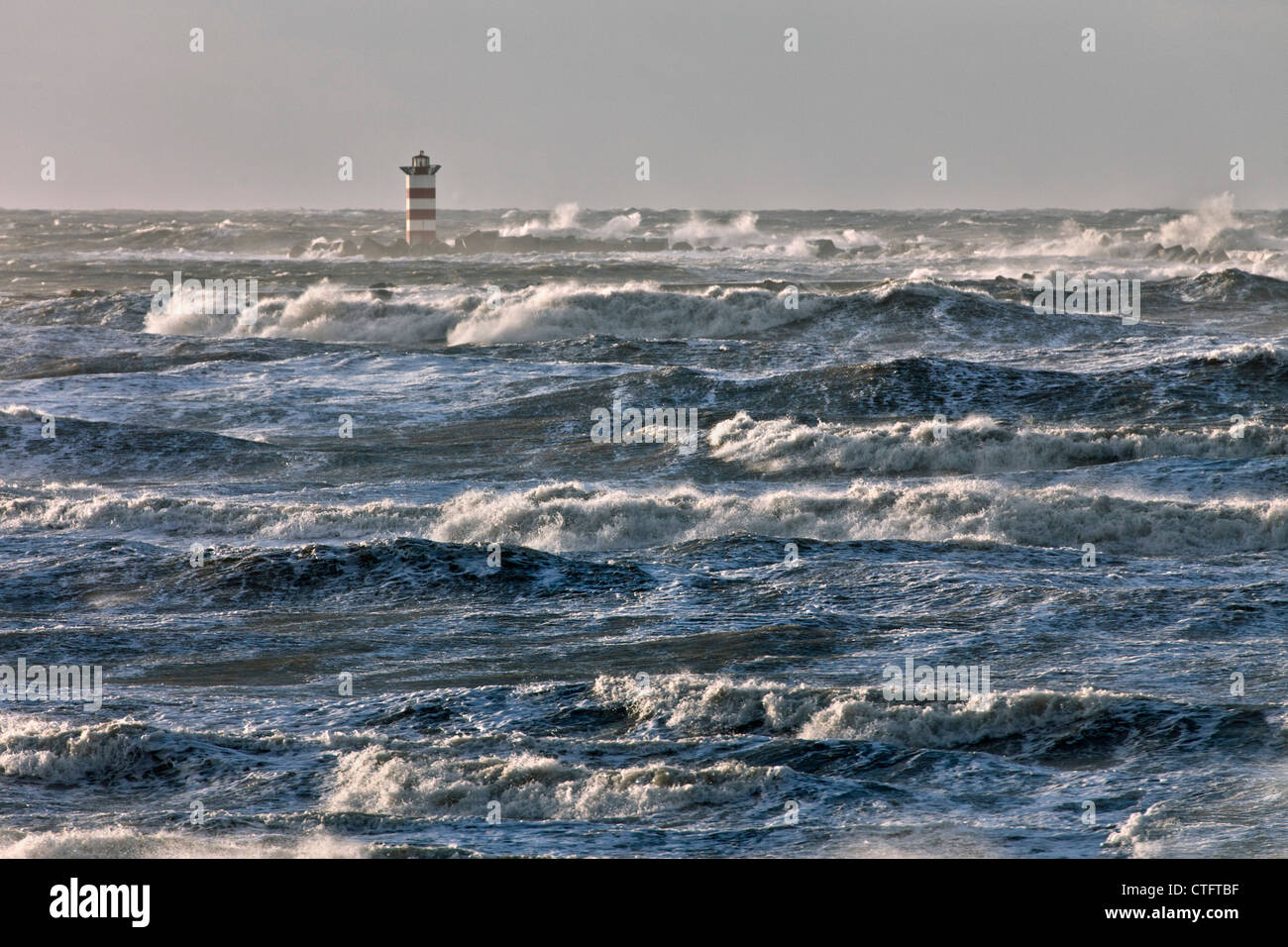 The Netherlands, IJmuiden, Storm. Waves crash against lighthouse or beacon. - Stock Image
