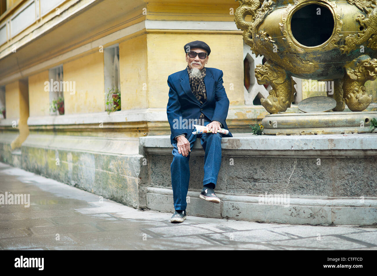 An old man in a blue suit, wearing an artist hat and sunglasses at a temple in Vietnam. - Stock Image