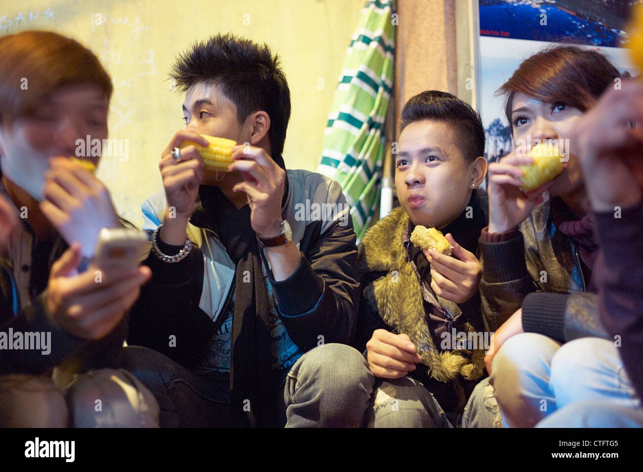 Young adults eating corn on the streets of Vietnam at night. - Stock Image