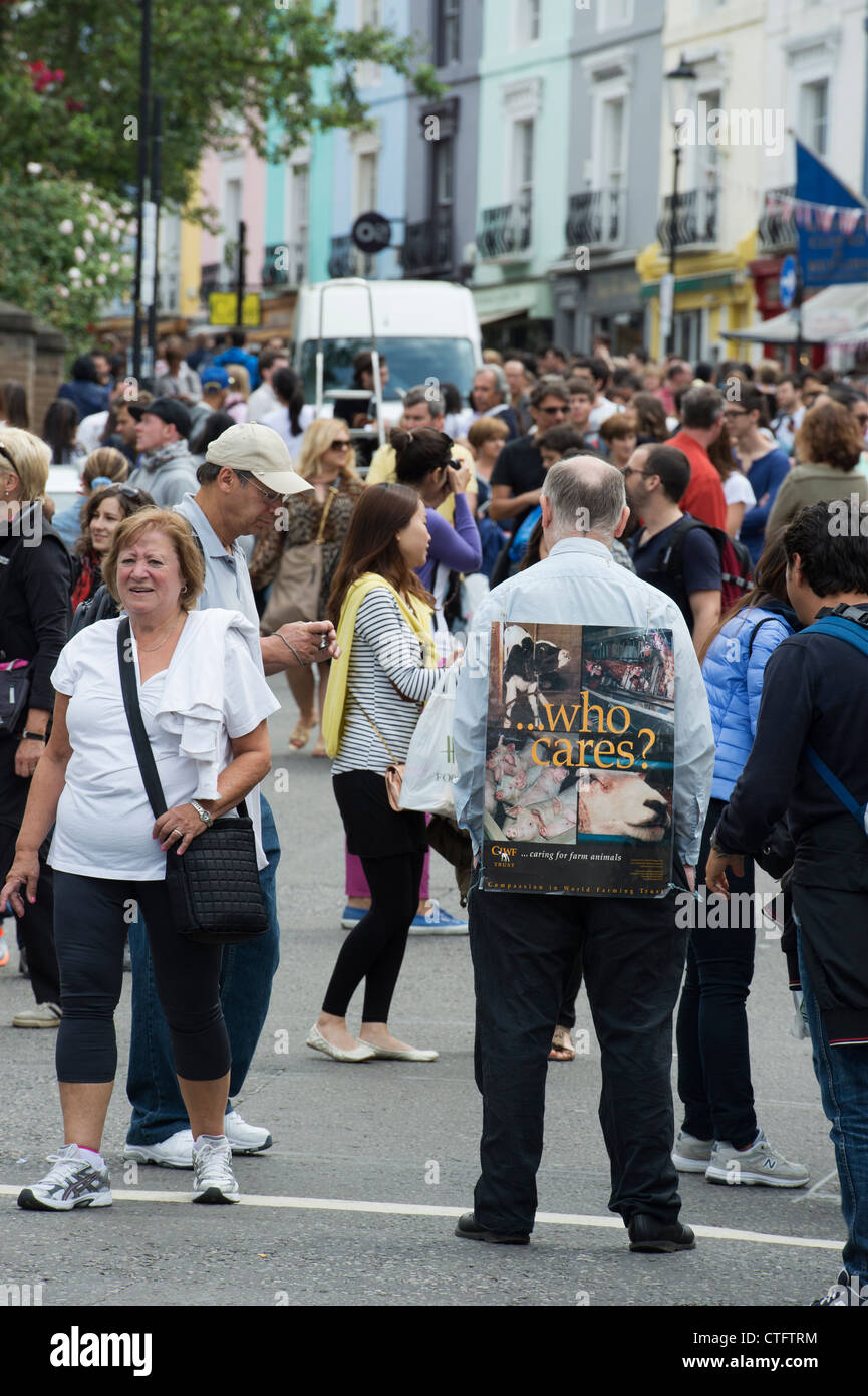 Farm Animal rights campaigner standing with a 'who cares' placard in Portobello Road market. London - Stock Image