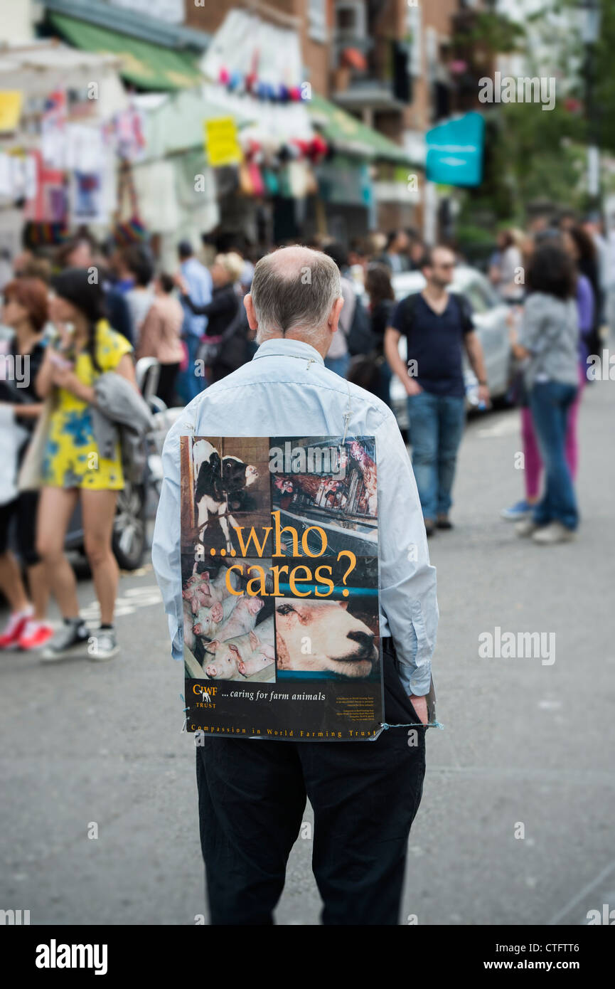 Farm Animal rights campaigner standing with a 'who cares' placard in Portobello Road. London - Stock Image