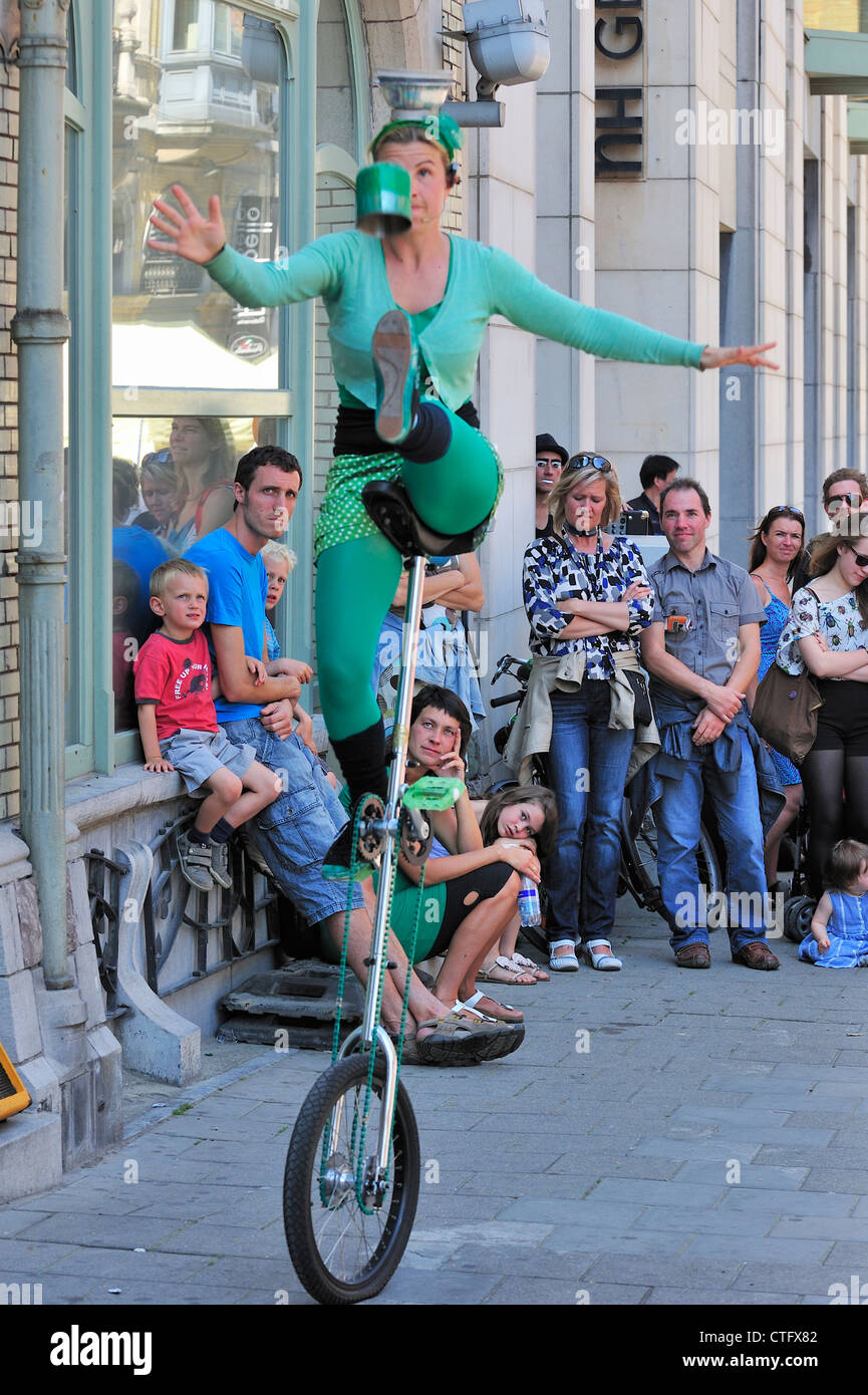 Woman juggling from unicycle as street animation at the Gentse Feesten / Ghent Festivities in summer, Belgium - Stock Image