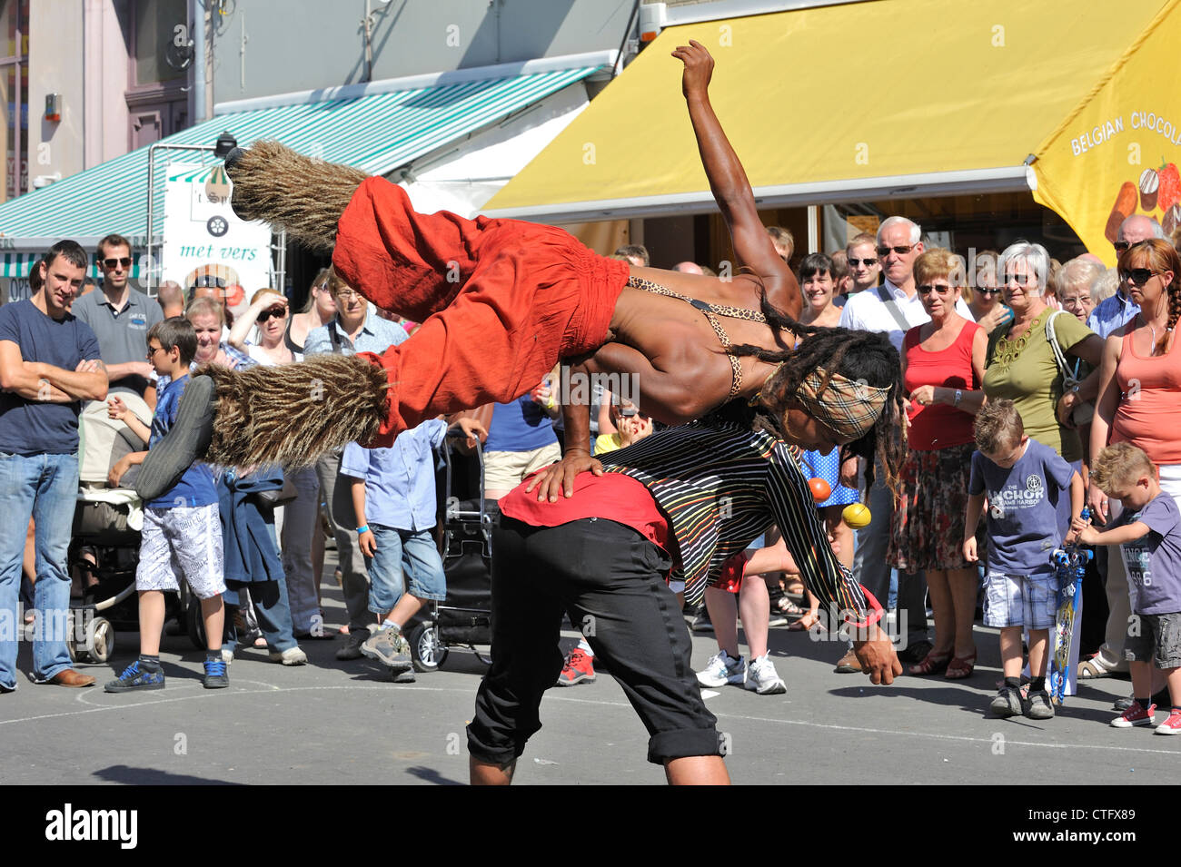Animation by two black street performers doing acrobatics at the Gentse Feesten / Ghent Festivities in summer, Belgium - Stock Image