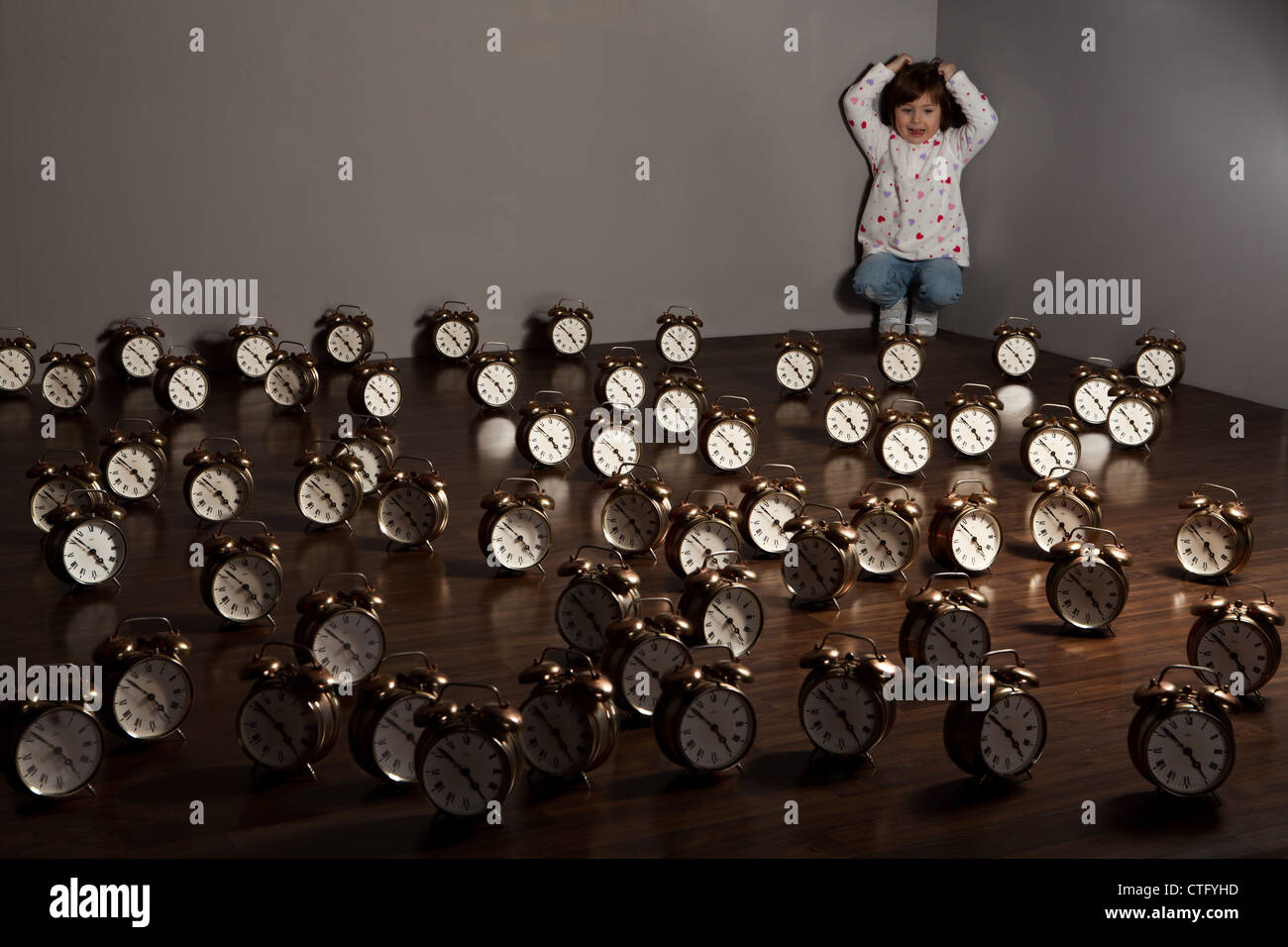 alarms,annoyed,bare,bells,brown,caucasian,child,children,clocks,corner,covered,female,floor,girl,large,lots,multiple,number,numerous,objects,quantity,room,scream,screaming,stressed,stressful,supported,synchronized,synchrony,time,times,walls,white - Stock Image
