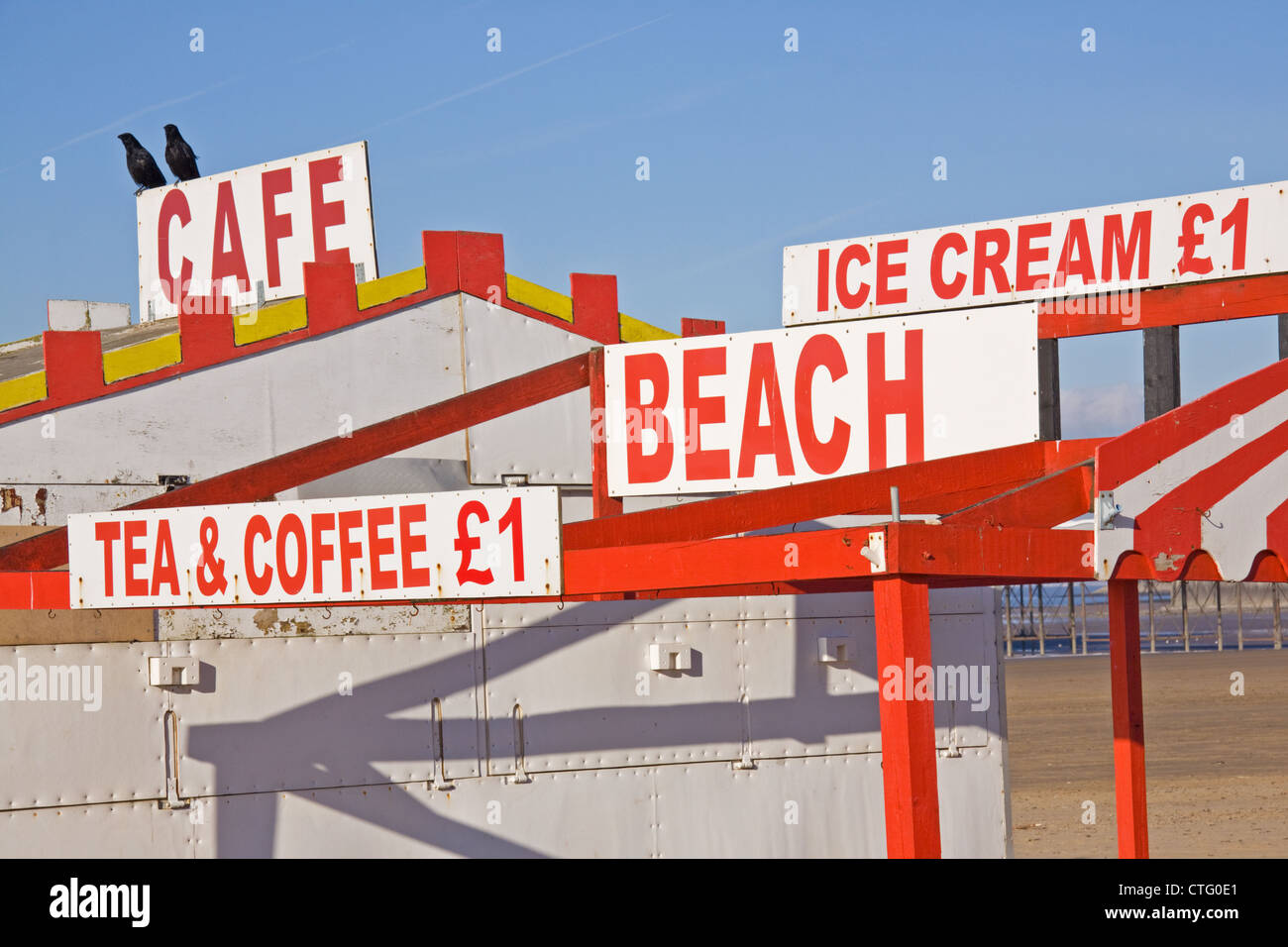 signs on a deserted english holiday beach advertising the wares of a seaside cafeteria closed for the winter