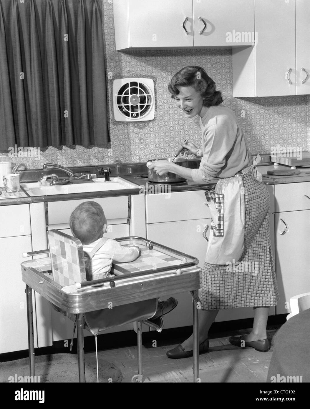 1950s WOMAN MOTHER IN HOME KITCHEN COOKING POT ON STOVE SMILING AT BABY CHILD IN HIGH CHAIR Stock Photo