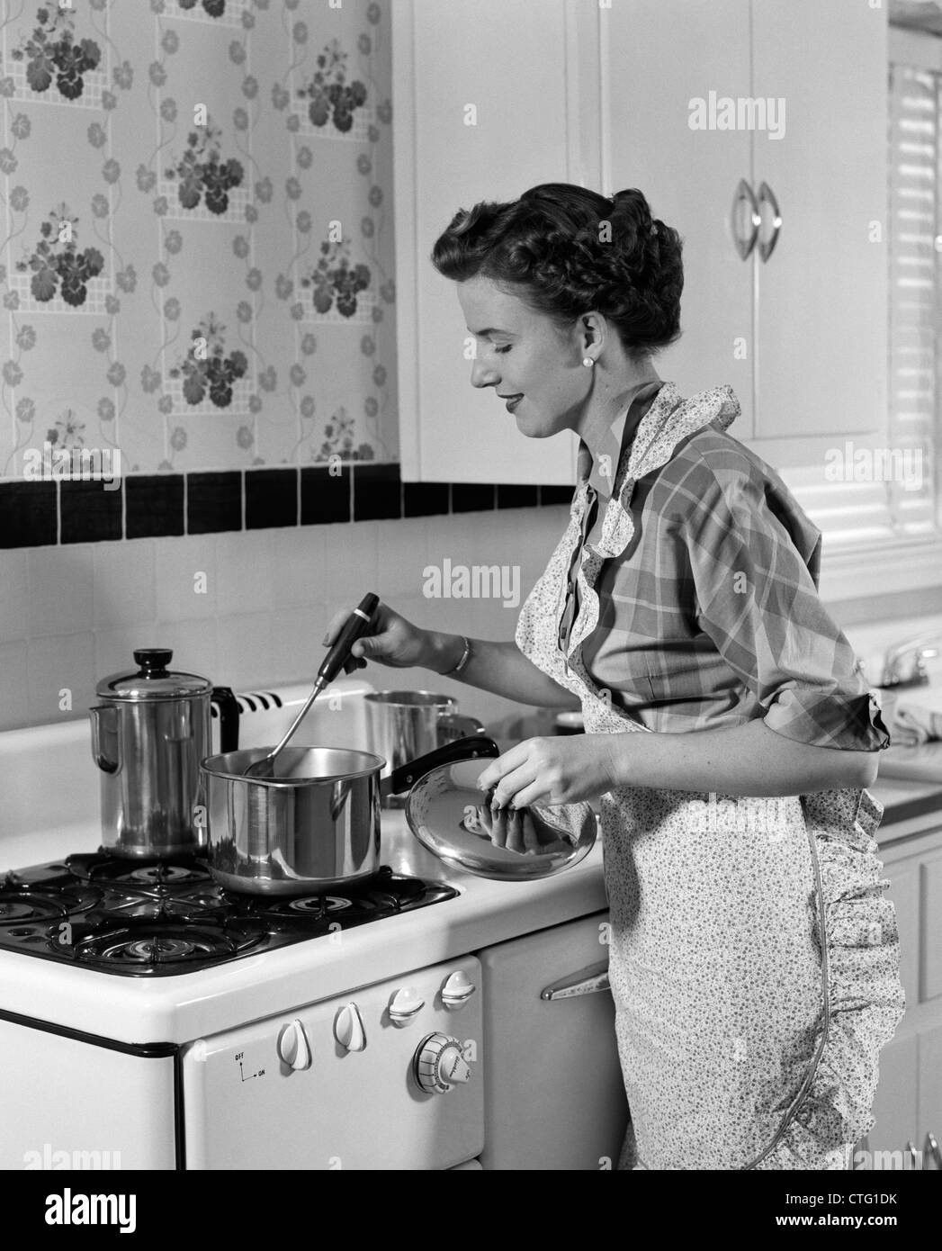 1950s HOUSEWIFE IN APRON STIRRING FOOD IN SAUCEPAN ON STOVE - Stock Image
