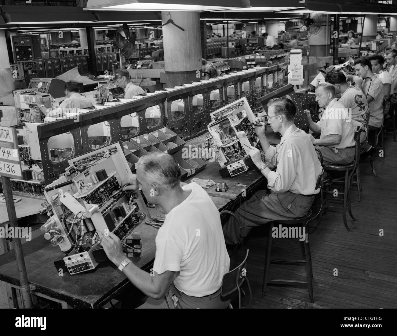 1950s MEN IN ELECTRONICS FACTORY WORKING ON TELEVISION ASSEMBLY LINE INDOOR - Stock Image