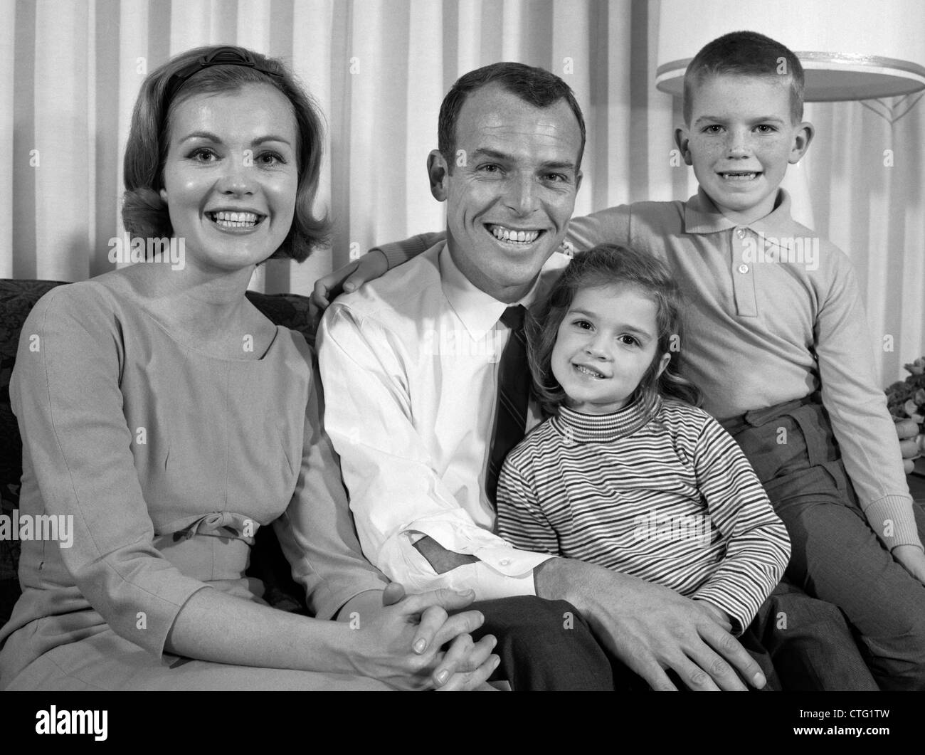 1960s SMILING FAMILY PORTRAIT MOTHER FATHER SON DAUGHTER LOOKING AT CAMERA - Stock Image