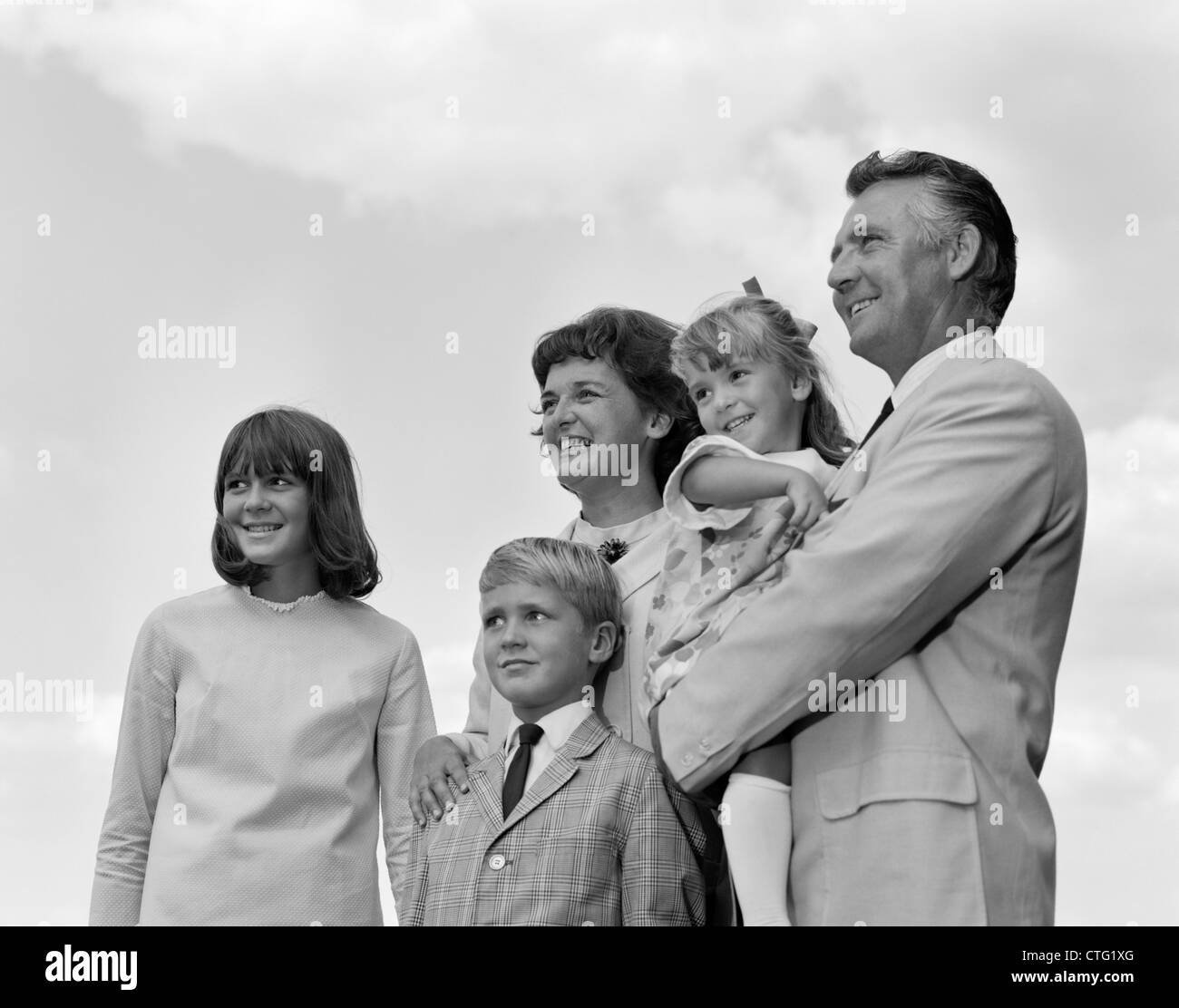 1960s PORTRAIT FAMILY OF FIVE OUTSIDE LOOKING OFF INTO DISTANCE - Stock Image