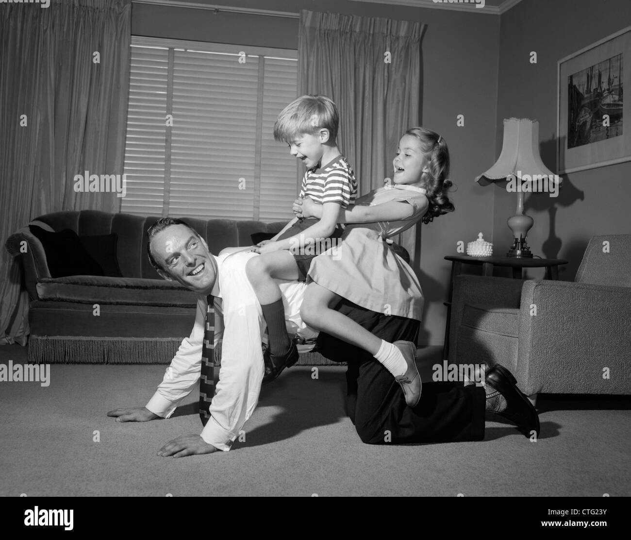 1950s 1960s DAD CARRYING BOY & GIRL PIGGYBACK ON LIVING ROOM FLOOR - Stock Image