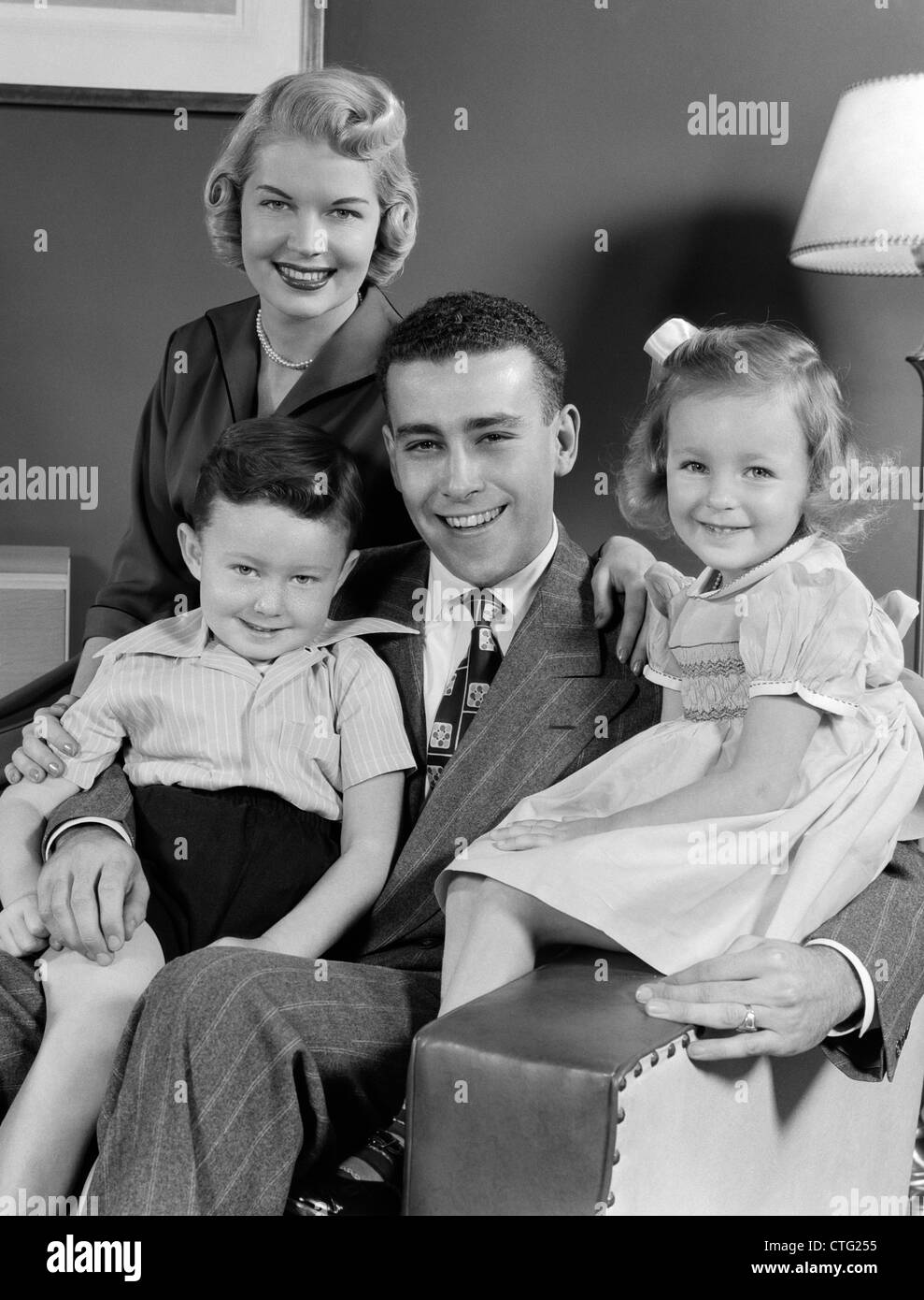 1940s 1950s FAMILY OF FOUR PORTRAIT SITTING IN LIVING ROOM CHAIR LOOKING AT CAMERA - Stock Image