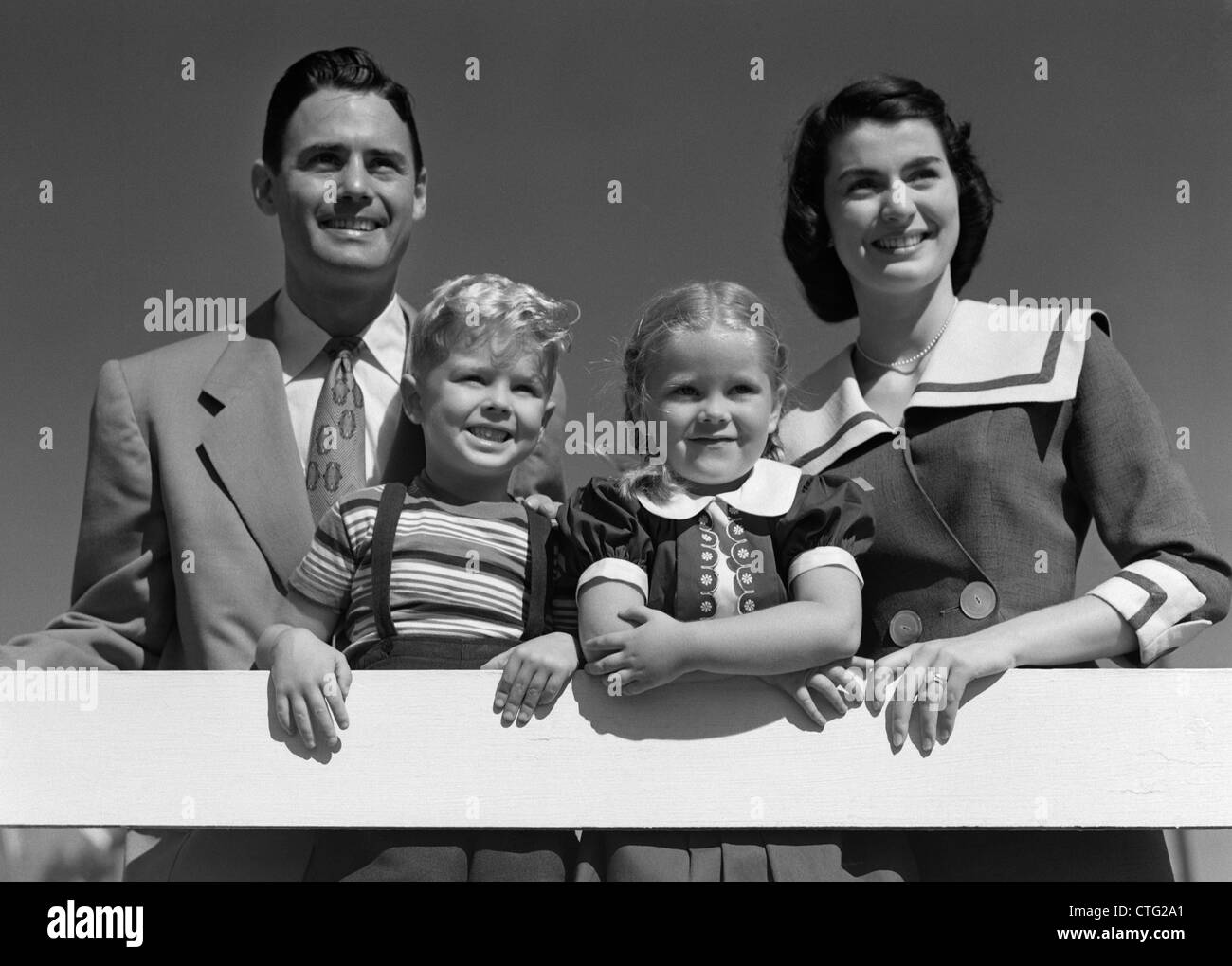 1950s PORTRAIT SMILING FAMILY FATHER MOTHER DAUGHTER SON STANDING TOGETHER BEHIND WHITE FENCE OUTDOOR - Stock Image