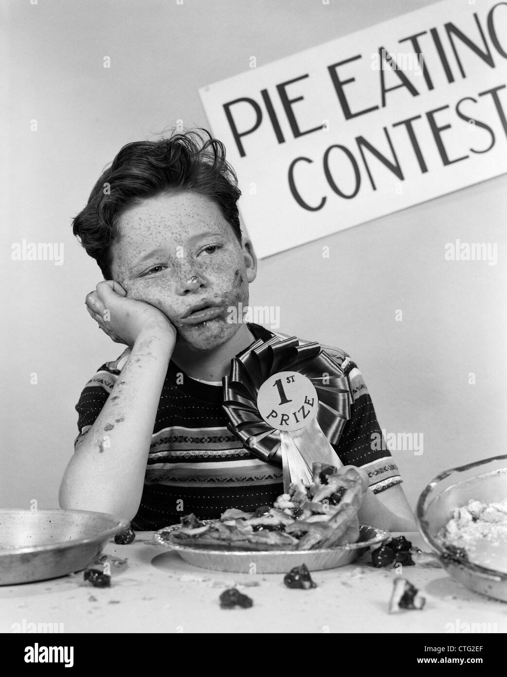 1950s BOY WINS 1ST PRIZE AT PIE-EATING CONTEST AND LOOKS SICK - Stock Image
