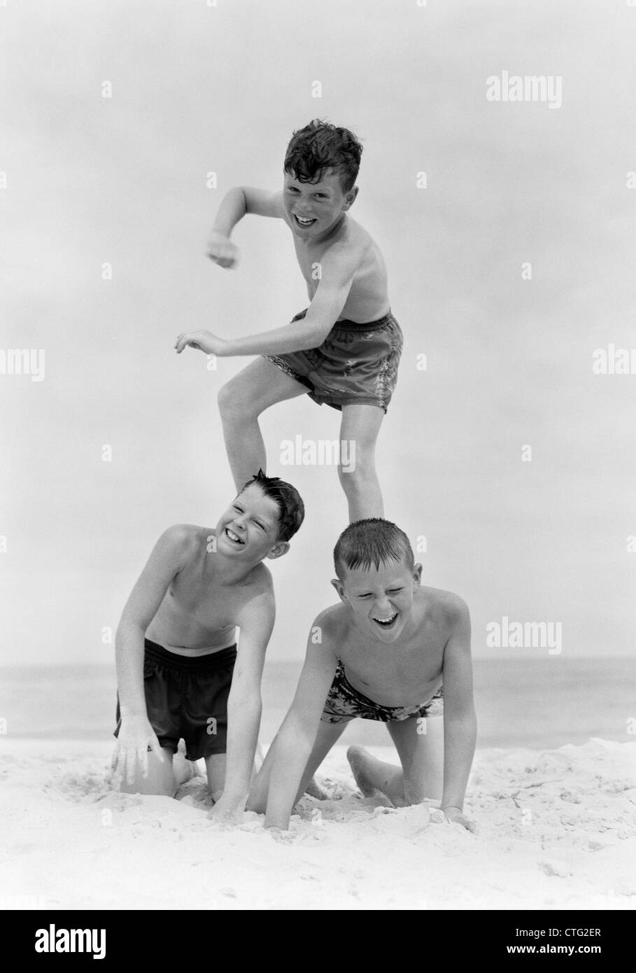 1950s THREE BOYS IN BATHING SUITS FORM A PYRAMID IN THE SAND ON THE BEACH - Stock Image