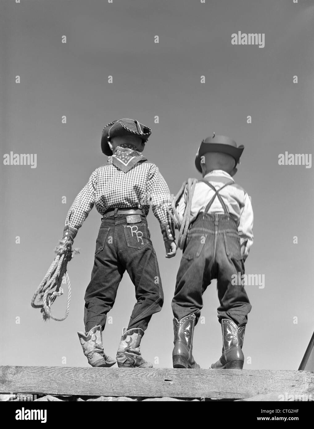 1950s BACK VIEW OF TWO BOYS DRESSED IN COWBOY COSTUME - Stock Image