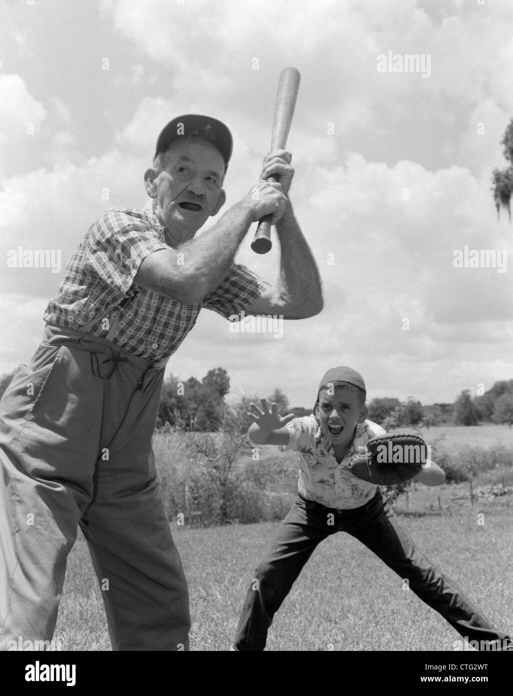 1950s GRANDFATHER AT BAT WITH BOY AS CATCHER PLAYING BASEBALL - Stock Image