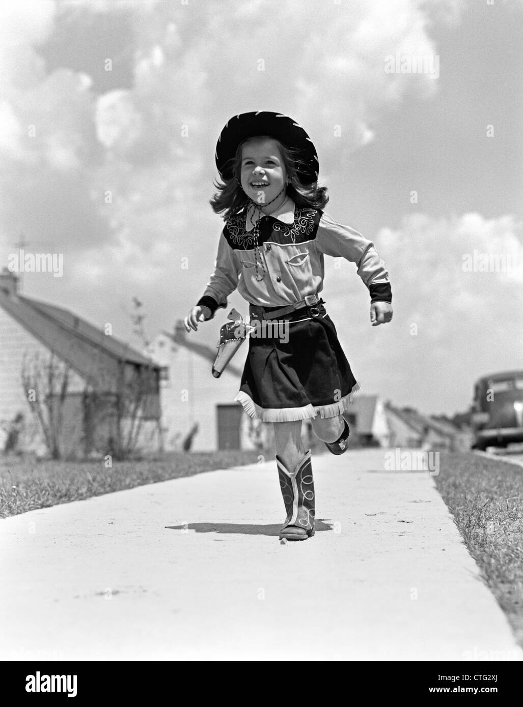 1950s GIRL IN COWGIRL OUTFIT RUNNING ON SIDEWALK TOWARDS CAMERA - Stock Image