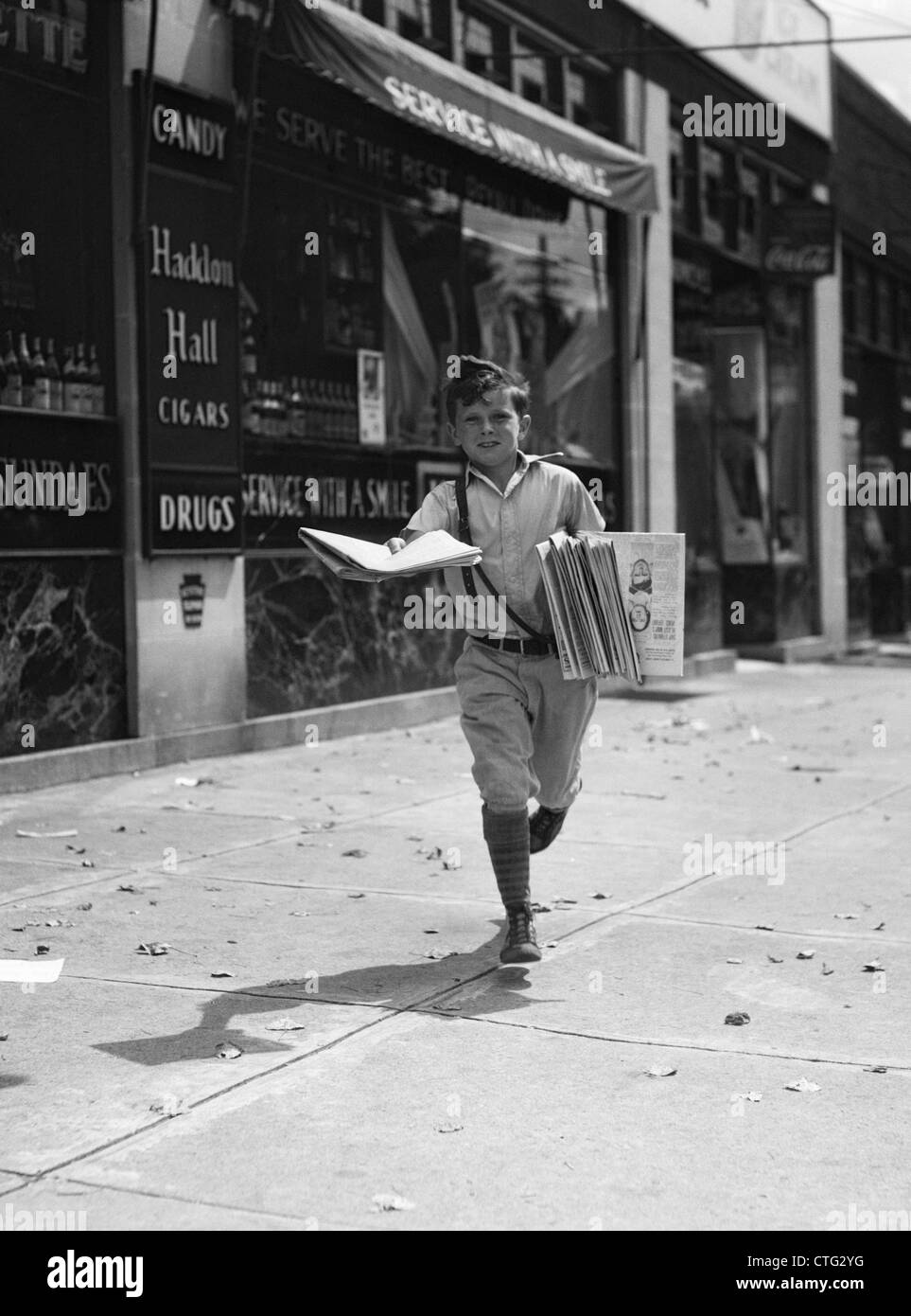 1930s NEWSPAPER BOY IN KNICKERS WALKING TOWARDS CAMERA ON STREET HOLDING PHILADELPHIA INQUIRER Stock Photo