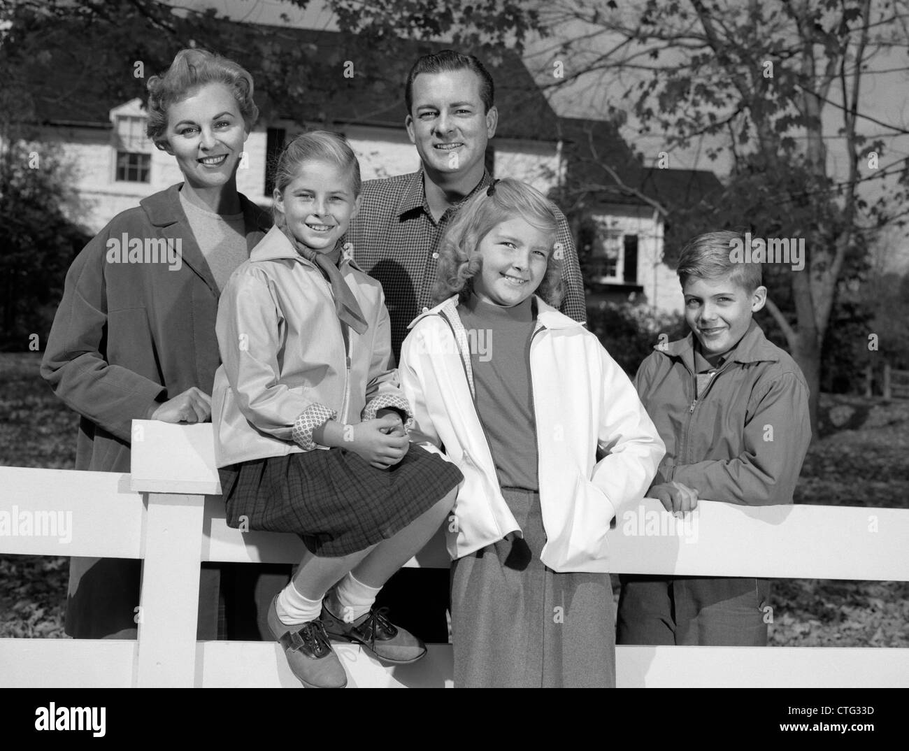 1960s PORTRAIT SMILING FAMILY FATHER MOTHER TWO DAUGHTERS SON BY WHITE FENCE IN FRONT OF SUBURBAN HOUSE IN AUTUMN - Stock Image