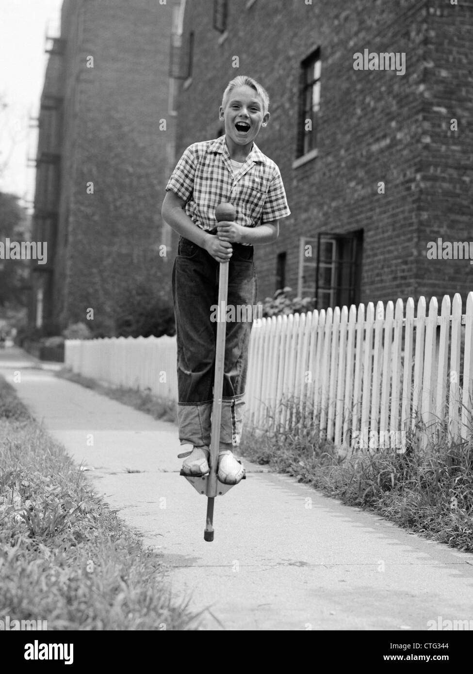 1960s BOY ON POGO STICK ON SIDEWALK - Stock Image