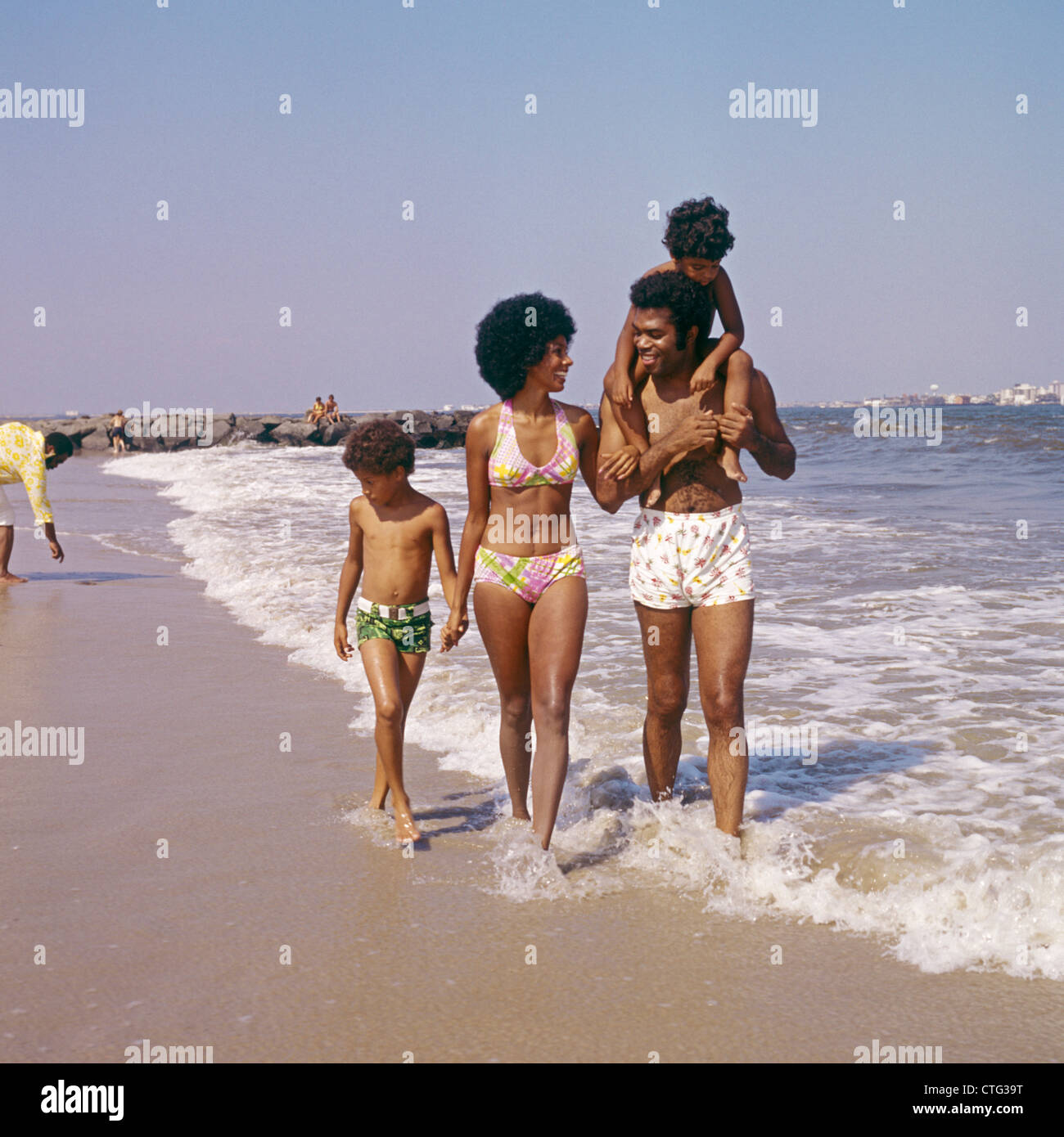 1970s AFRICAN-AMERICAN FAMILY OF FOUR WALKING ON BEACH - Stock Image