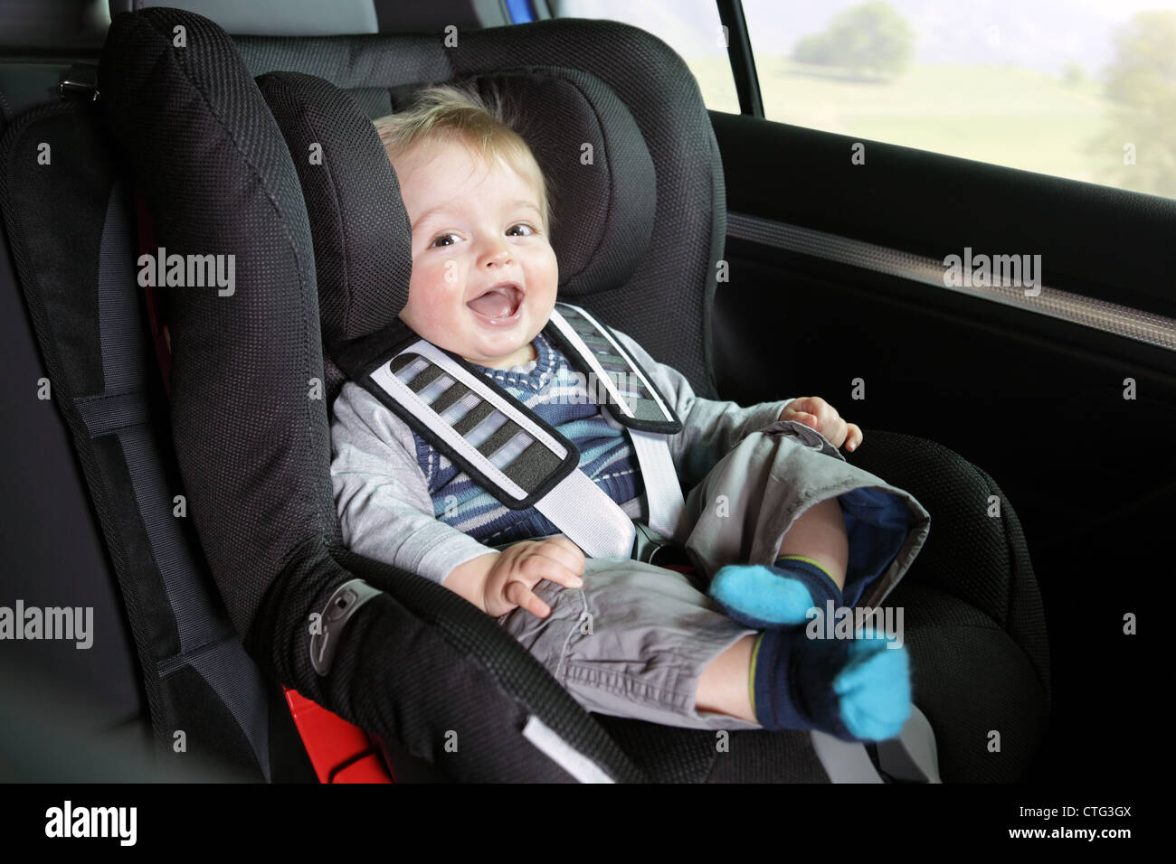 Baby boy in a child safety car seat - Stock Image