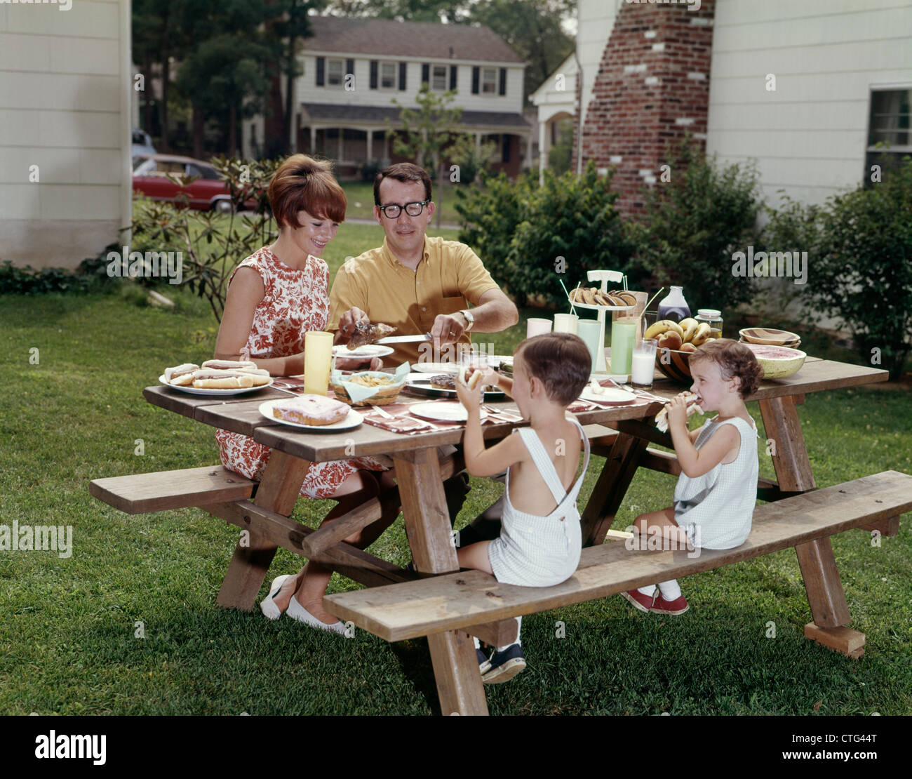 Backyard Picnic 1960s family of four at backyard picnic table stock photo: 49526984