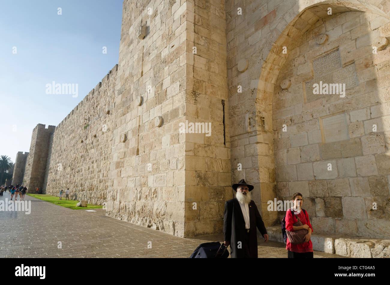 Orthodox Jew and young woman walking along the city walls. Jaffa gate. Jerusalem. Israel. - Stock Image