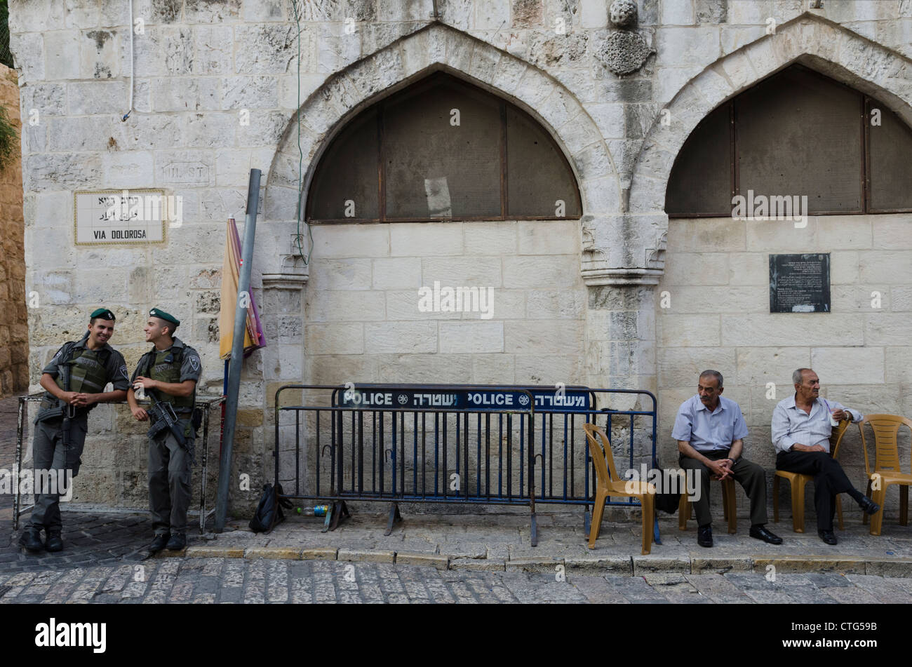 two Israeli border patrols and two elderli Palestinians at the fifth station of the Via Dolorosa. Jerusalem Old - Stock Image