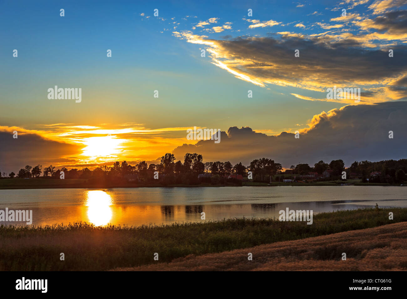 Lake Landscape with sunset reflections on the surface of water. - Stock Image