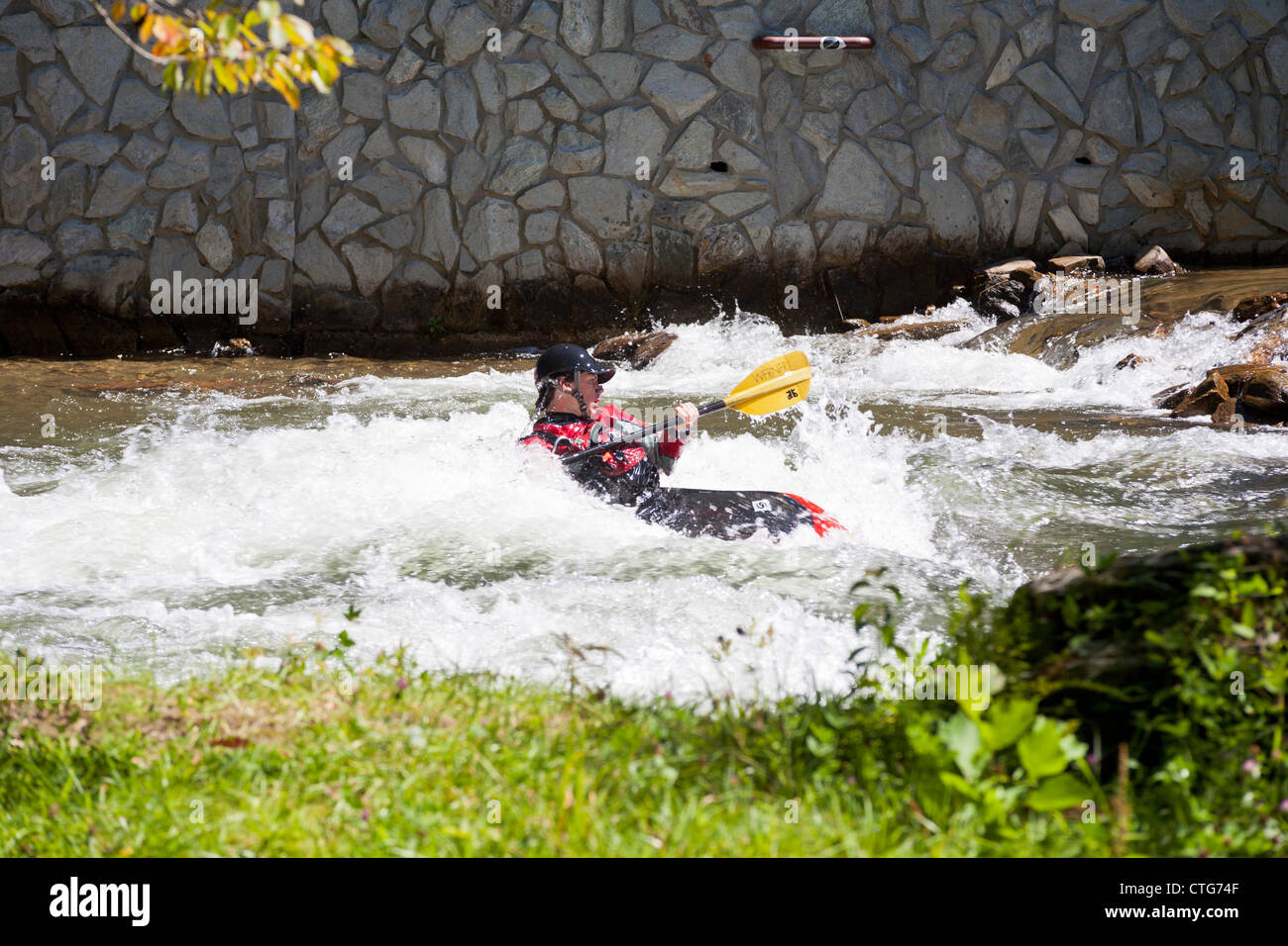 Whitewater kayaker manouvering kayak in rapids at the Nantahala Outdoor Center in North Carolina - Stock Image