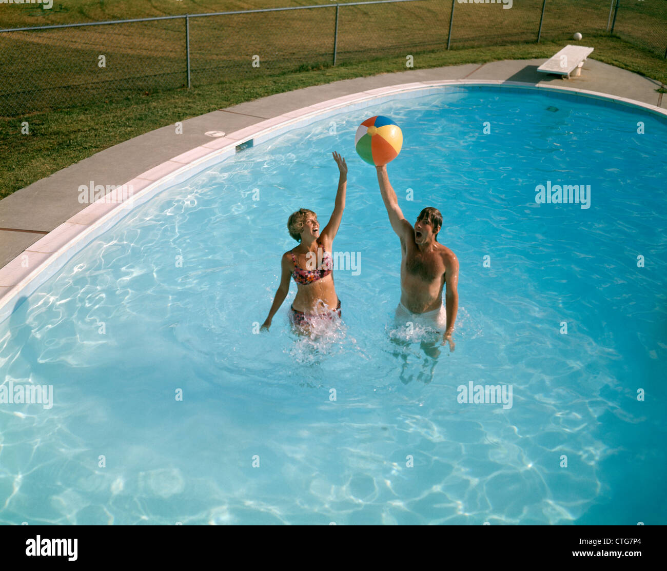 1980 1980s man woman couple jumping up beach ball backyard for Swimming pool photos