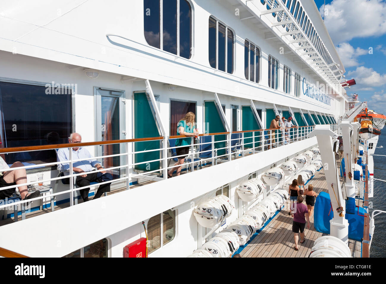 Cruise ship passengers on balconies wait for ship to leave port in Jacksonville, Florida, USA - Stock Image