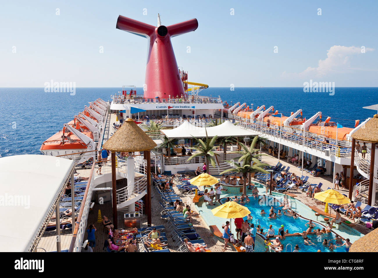 Cruise passengers enjoying the sun on deck of Carnival Fascination cruise ship - Stock Image