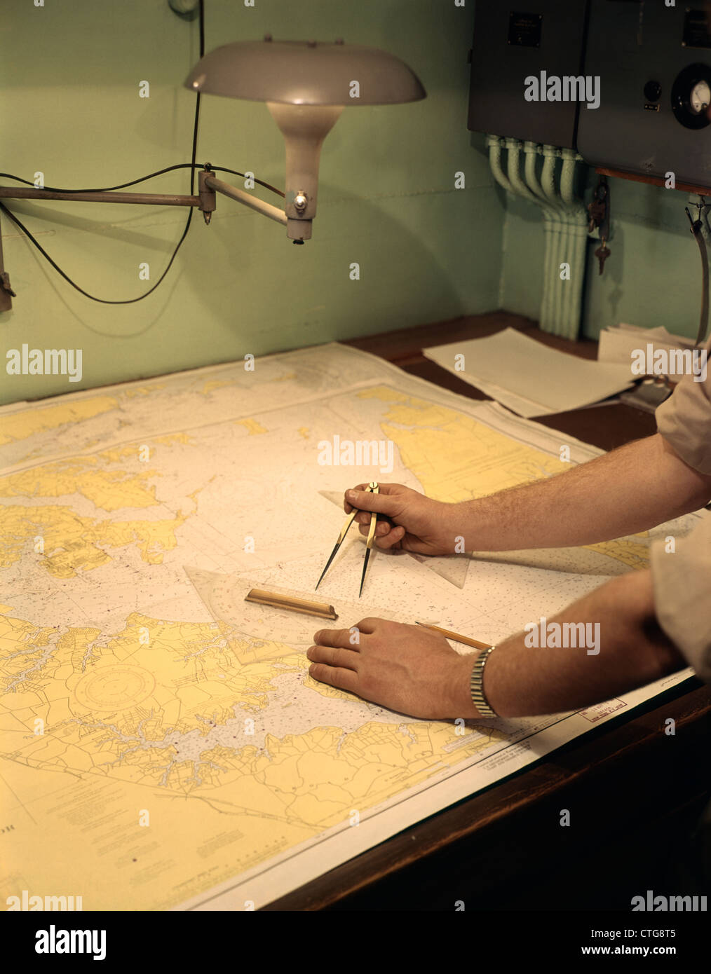 1960s MALE HANDS USING NAUTICAL NAVIGATION TOOLS COMPASS MAP CHART CHARTING A COURSE - Stock Image