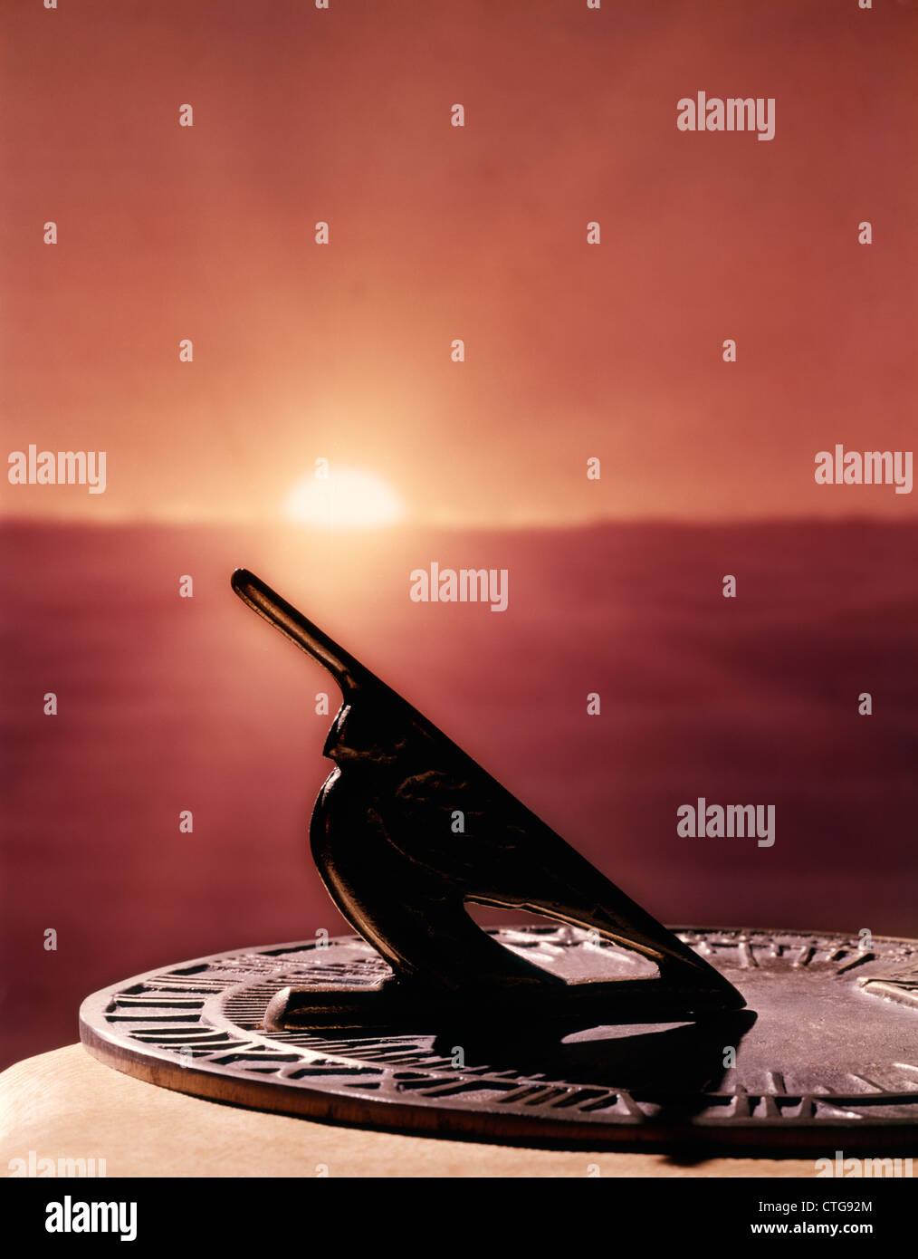 SETTING SUN CASTING A SHADOW ON SUNDIAL - Stock Image