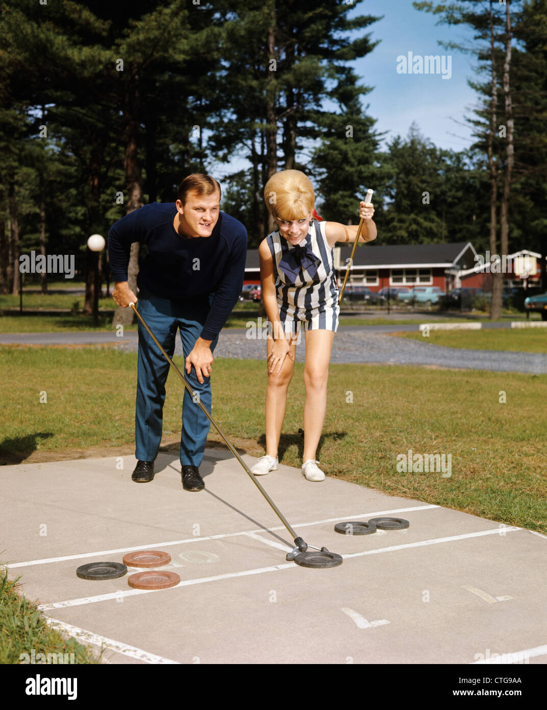 1960s COUPLE PLAYING SHUFFLEBOARD POCONO MOUNTAIN RESORT WOMAN BLONDE BOUFFANT TEASED HAIR FASHION RETRO - Stock Image