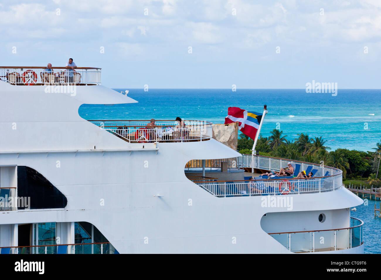 Cruise ship passengers lounging on multiple decks at port in Nassau, Bahamas - Stock Image