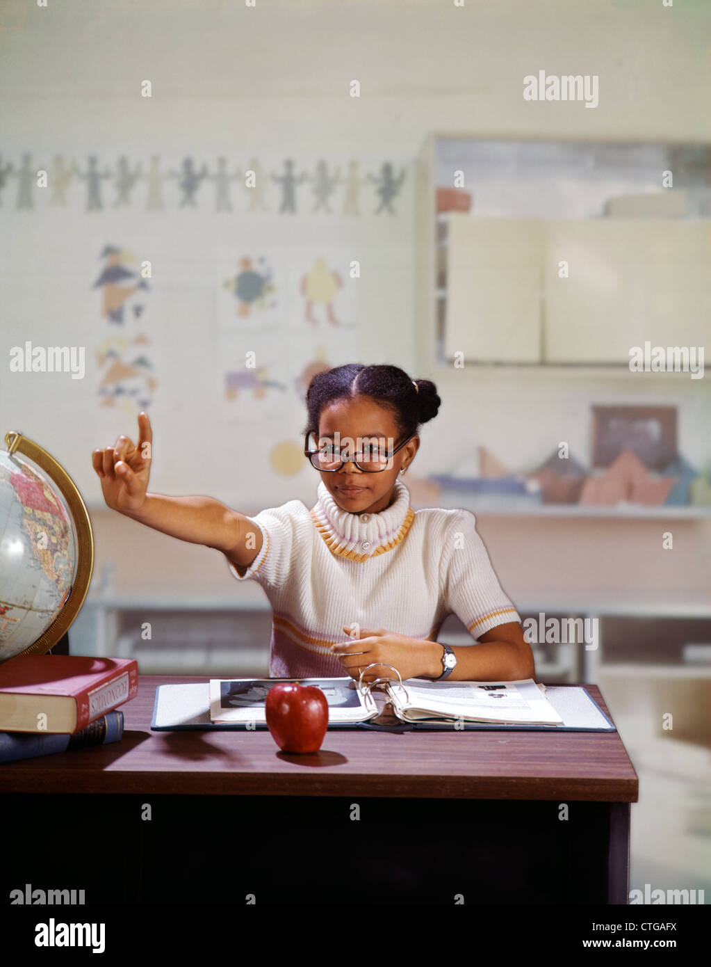 1970s AFRICAN AMERICAN GIRL HOLDING UP HAND ASKING QUESTION PLAYING TEACHER IN ELEMENTARY SCHOOL CLASSROOM - Stock Image