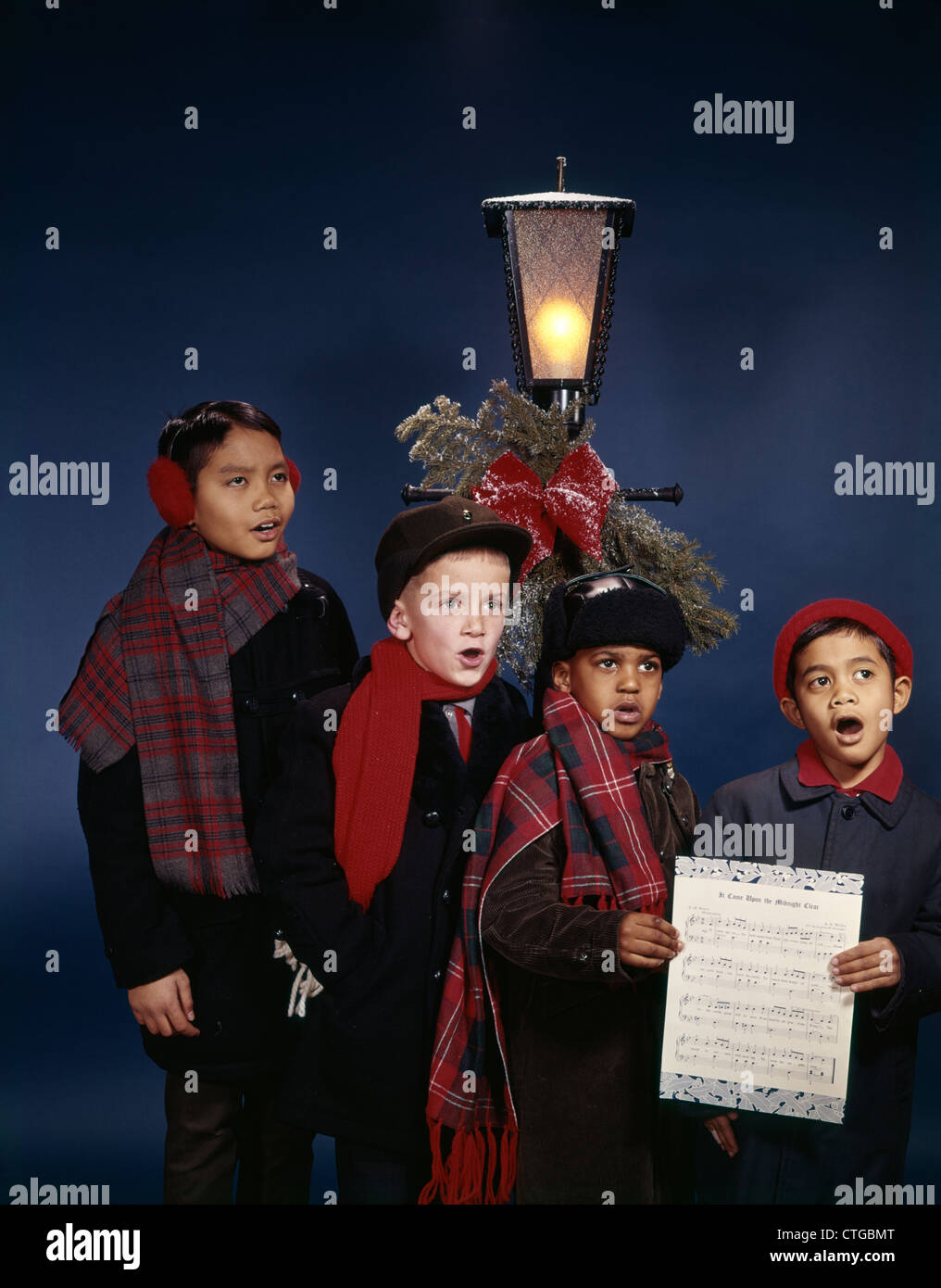 1960s GROUP JUVENILE BOYS SINGING CHRISTMAS CAROLS UNDER LAMP POST RETRO ETHNIC DIVERSITY MULTI-ETHNIC RACIAL MIX - Stock Image