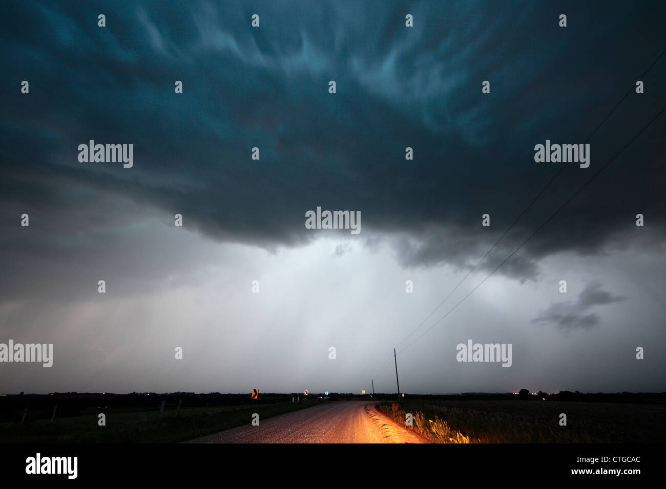 A squall line thunderstorm darkens the late afternoon sky over a country road, with heavy rain and strong winds. - Stock Image