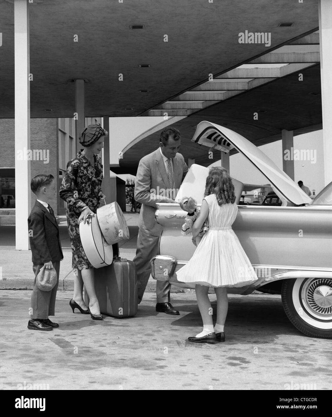 1950s 1960s FAMILY OF FOUR PACKING AUTOMOBILE TRUNK WITH LUGGAGE & HATBOXES - Stock Image