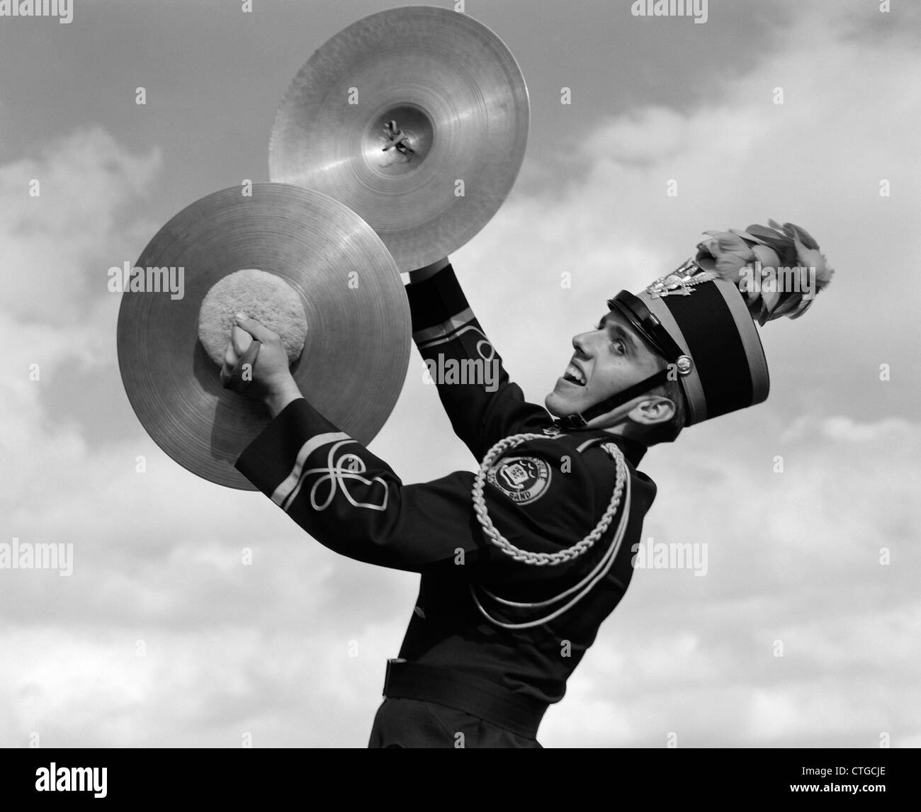 1960s PORTRAIT OF BOY IN BAND UNIFORM PLAYING INSTRUMENT CYMBALS OUTDOORS - Stock Image