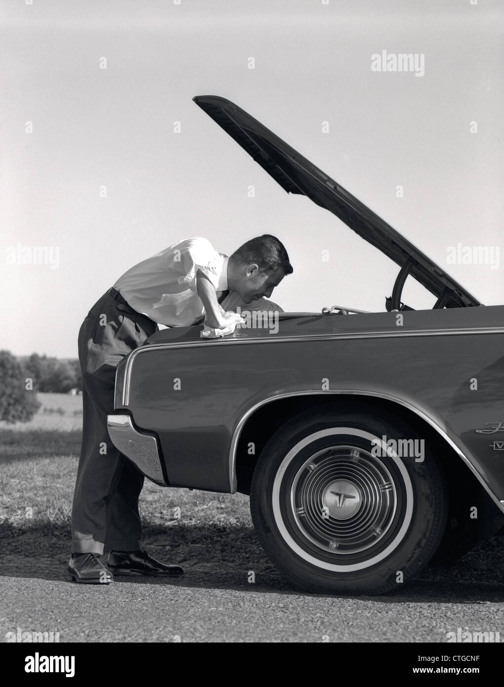 1960s SIDE VIEW OF MAN IN SHIRT & TIE LOOKING UNDER HOOD OF CAR PULLED UP ON SIDE OF ROAD - Stock Image