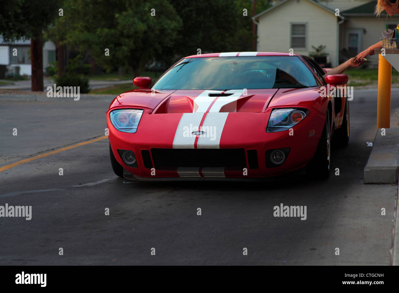 Red And White Striped Ford Gt Sports Car Making Transaction At Drive Through Window
