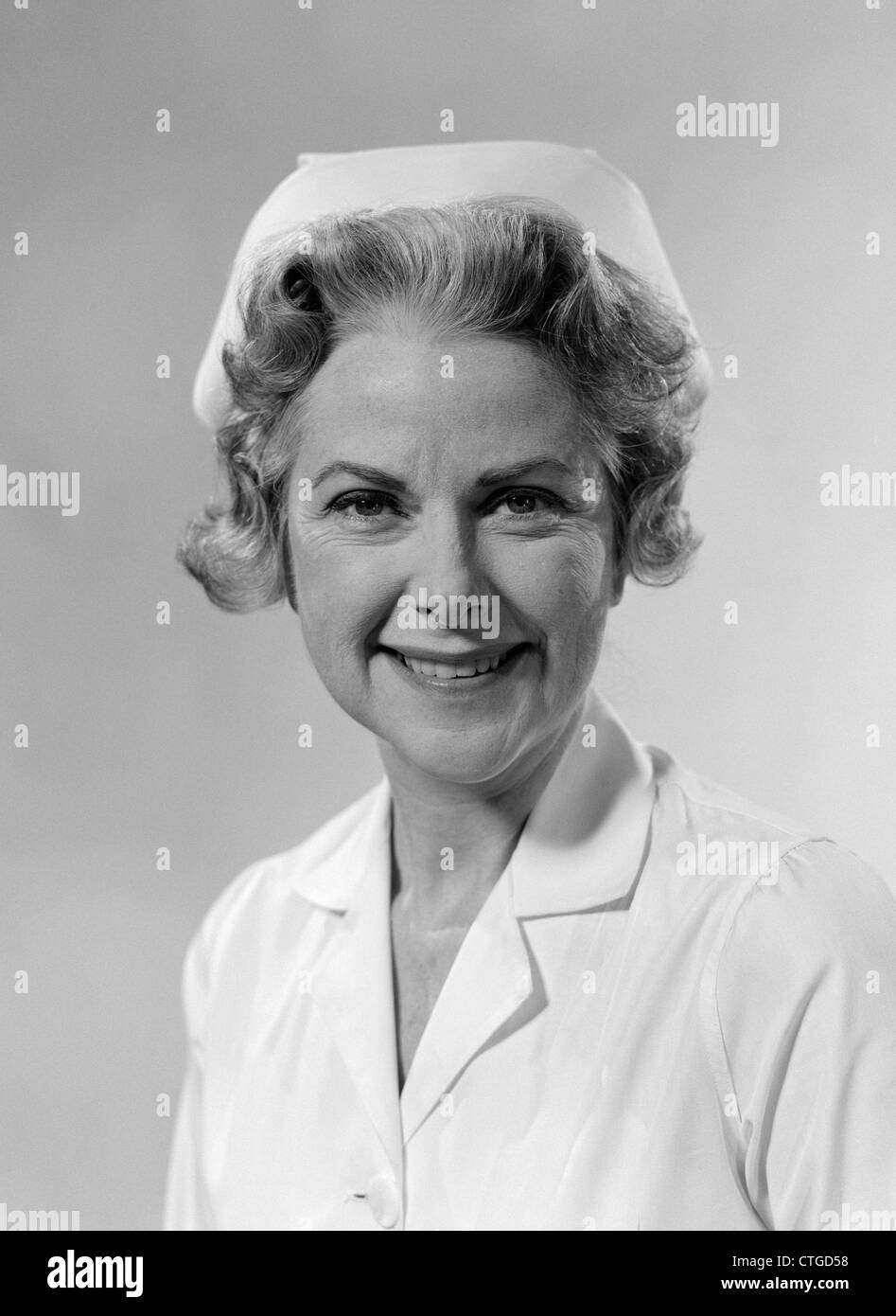 1960s PORTRAIT OF WOMAN NURSE SMILING WEARING WHITE CAP AND UNIFORM STUDIO INDOOR - Stock Image