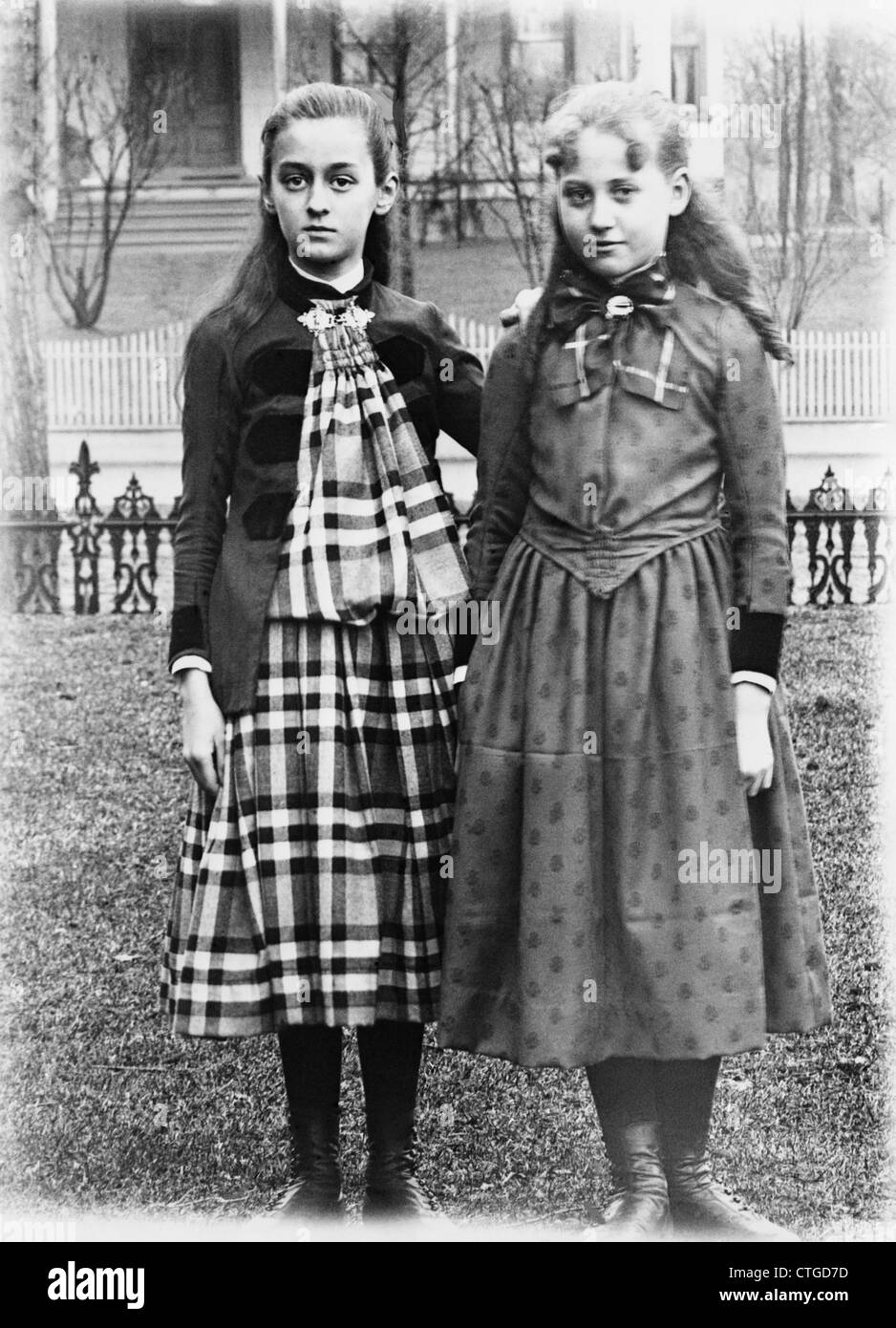 1880s 1900s 1890s TURN OF THE CENTURY PORTRAIT TWO GIRLS POSING STANDING ARM IN ARM ON LAWN BACKYARD - Stock Image