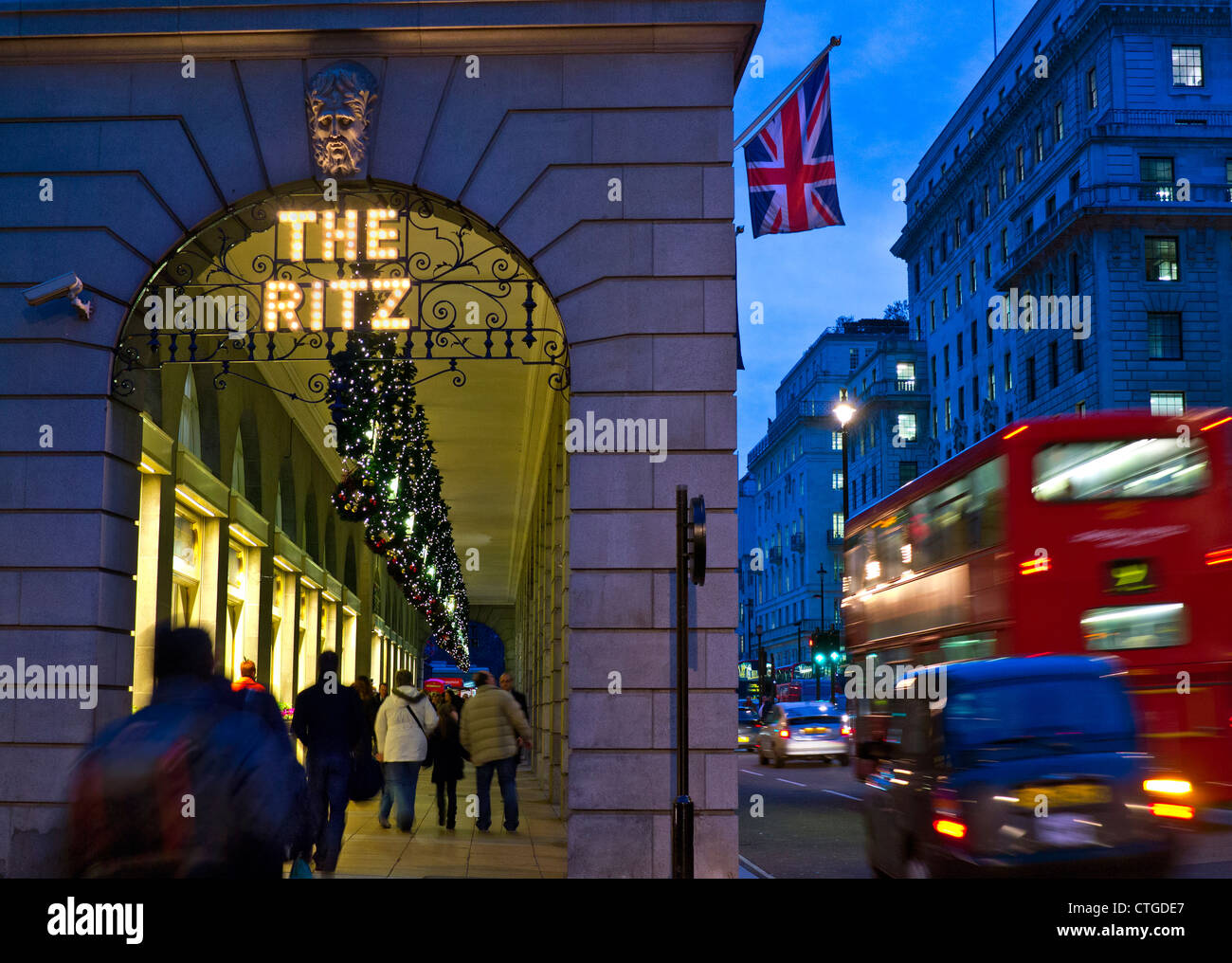 The Ritz Hotel at Christmas with Union Jack flag shoppers and passing red buses Piccadilly London - Stock Image