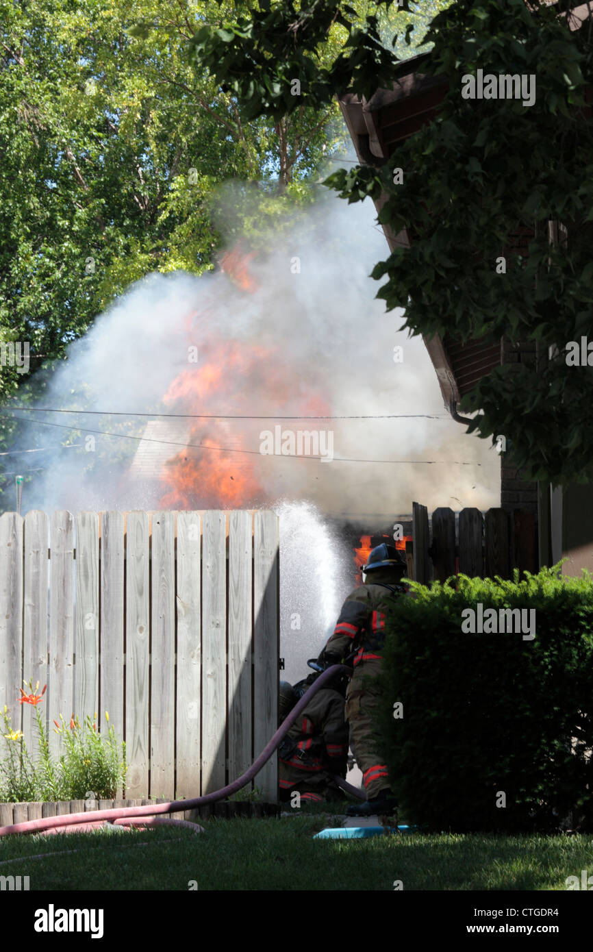 Firefighters use a water hose to extinguish a garage fire. - Stock Image